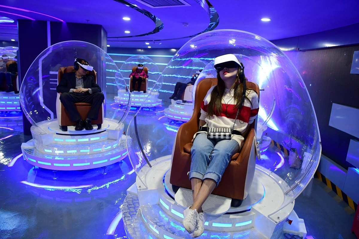 People wearing virtual reality (VR) headsets watch films at a newly opened VR cinema by Er Dong Pictures in Beijing, China March 27, 2019. Picture taken March 27, 2019. Lin Hui/Beijing Youth Daily via REUTERS ATTENTION EDITORS - THIS IMAGE WAS PROVIDED BY A THIRD PARTY. CHINA OUT. - RC187422FF70