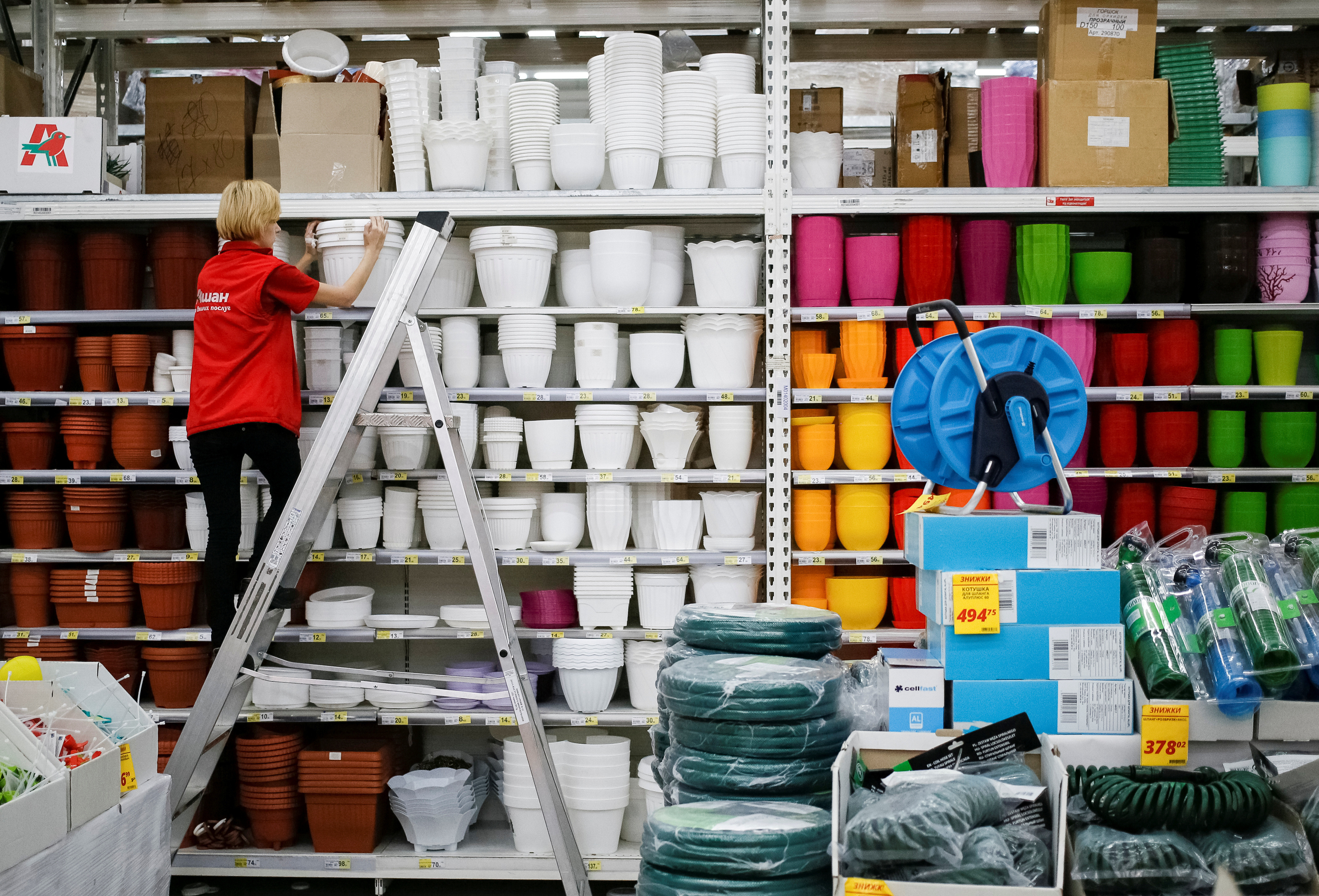 An employee stacks shelves with plastic containers at a supermarket in Kiev, Ukraine, August 7, 2016.