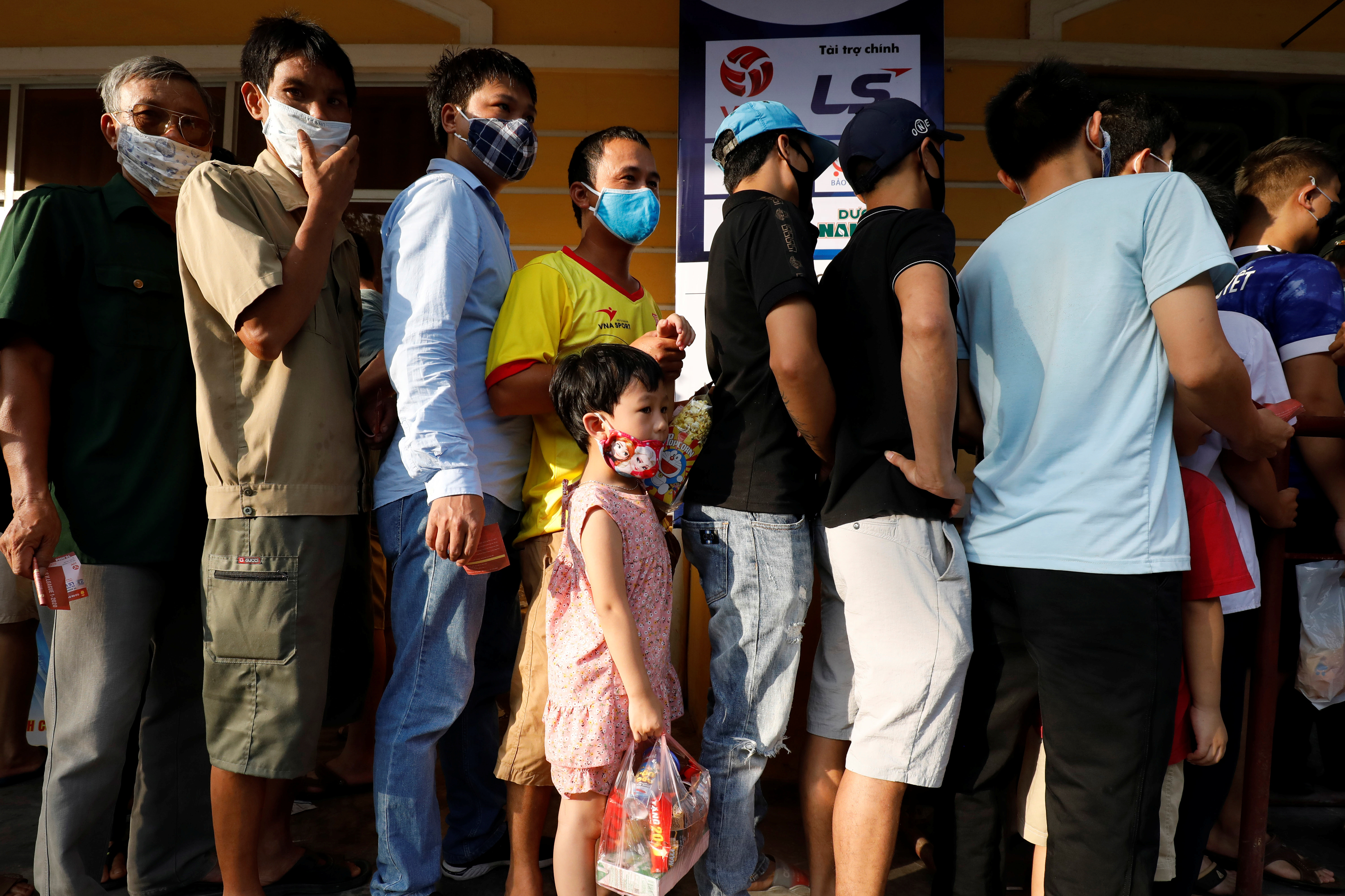 Soccer fans wearing protective masks line up before entering for a soccer match between Viettel and Duoc Nam Ha Nam Dinh of the V.League, the national soccer league, after the Government eased nationwide lockdown following the coronavirus disease (COVID-19) outbreak in Nam Dinh province, Vietnam June 5, 2020. REUTERS/Kham - RC223H98XD33