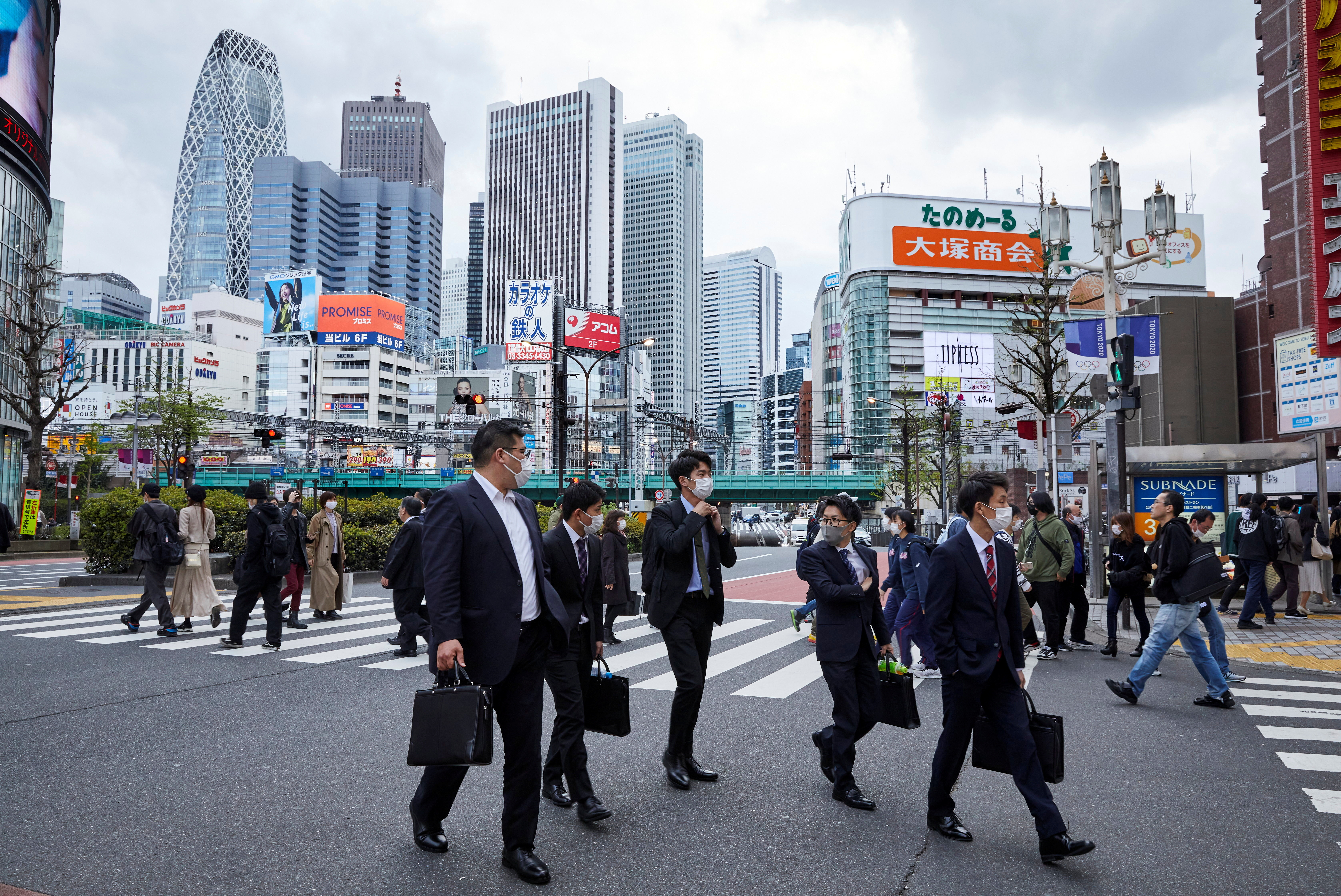 Passersby wearing protective masks during the COVID-19 pandemic walk on the street at Shinjuku district in Tokyo, Japan April 6, 2021.