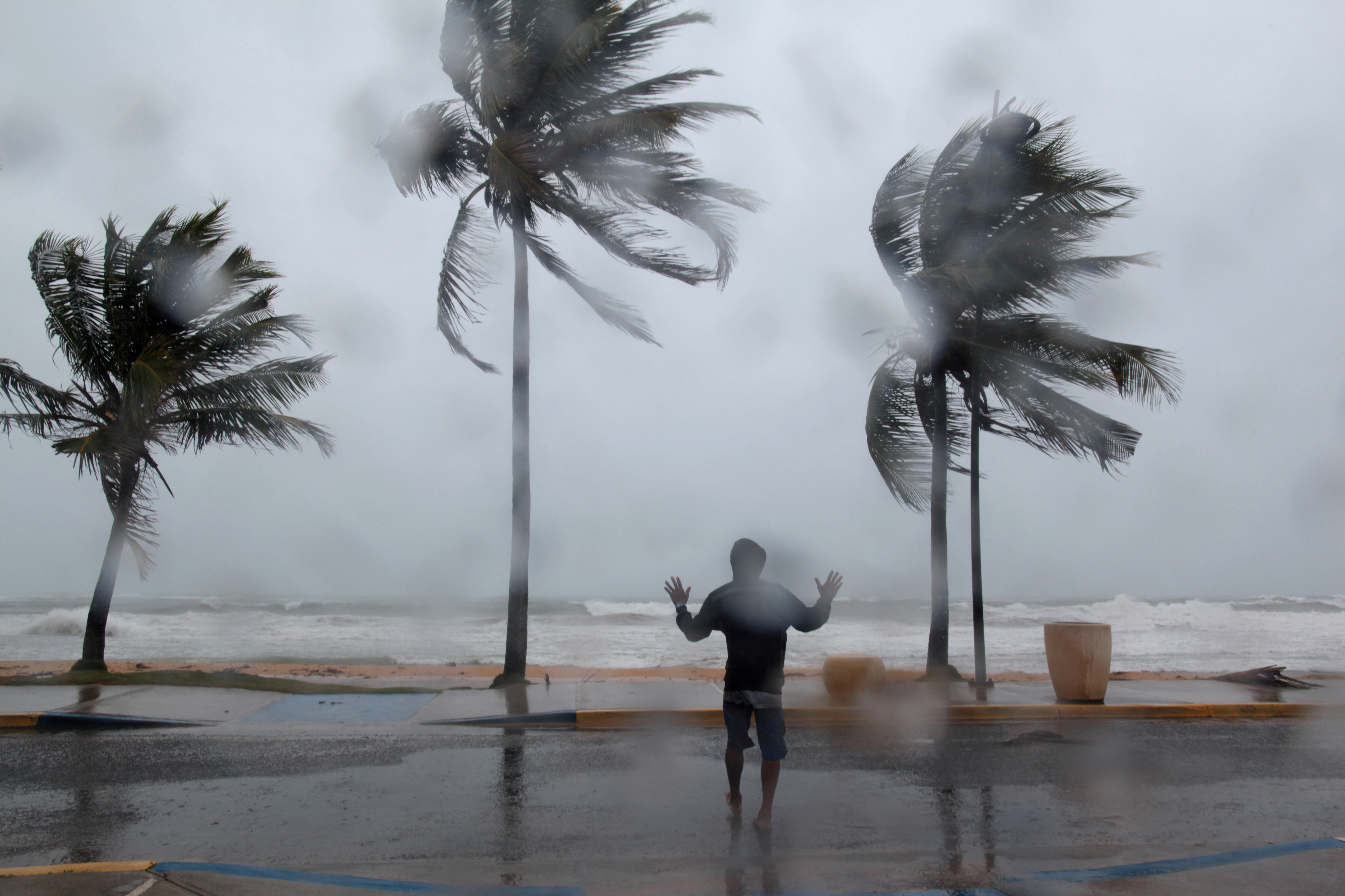A man reacts in the winds and rain as Hurricane Irma slammed across islands in the northern Caribbean on Wednesday, in Luquillo, Puerto Rico September 6, 2017.  REUTERS/Alvin Baez     TPX IMAGES OF THE DAY - RC14353ED7A0
