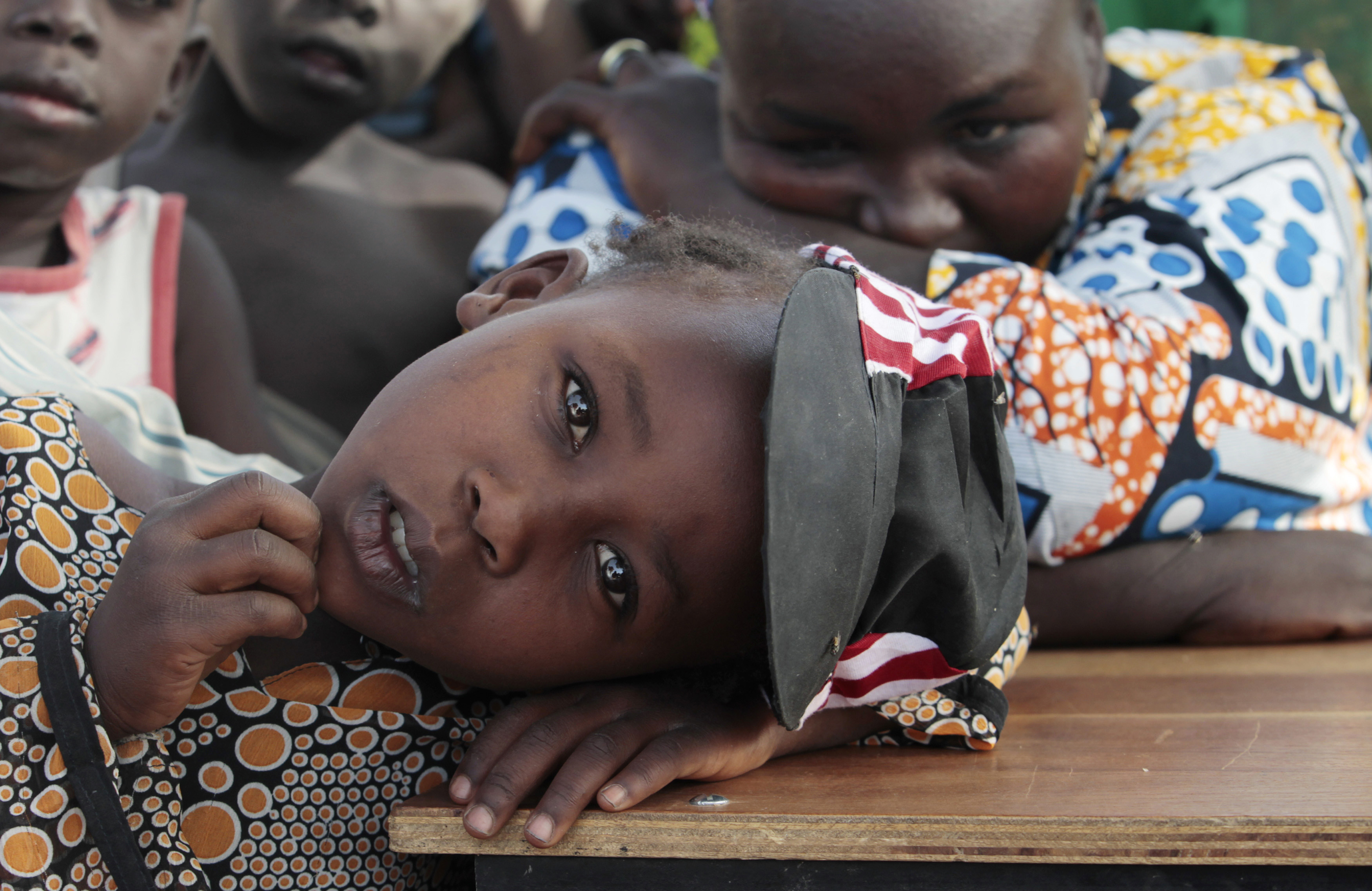 A girl displaced as a result of Boko Haram attack in the northeast region of Nigeria, rests her head on a desk at Maikohi secondary school camp for internally displaced persons (IDP) in Yola, Adamawa State January 13, 2015. Boko Haram says it is building an Islamic state that will revive the glory days of northern Nigeria's medieval Muslim empires, but for those in its territory life is a litany of killings, kidnappings, hunger and economic collapse. Picture taken January 13, 2015. To match Insight NIGERIA-BOKOHARAM/     REUTERS/Afolabi Sotunde (NIGERIA - Tags: CIVIL UNREST SOCIETY EDUCATION) - GM1EB1K0WBG01