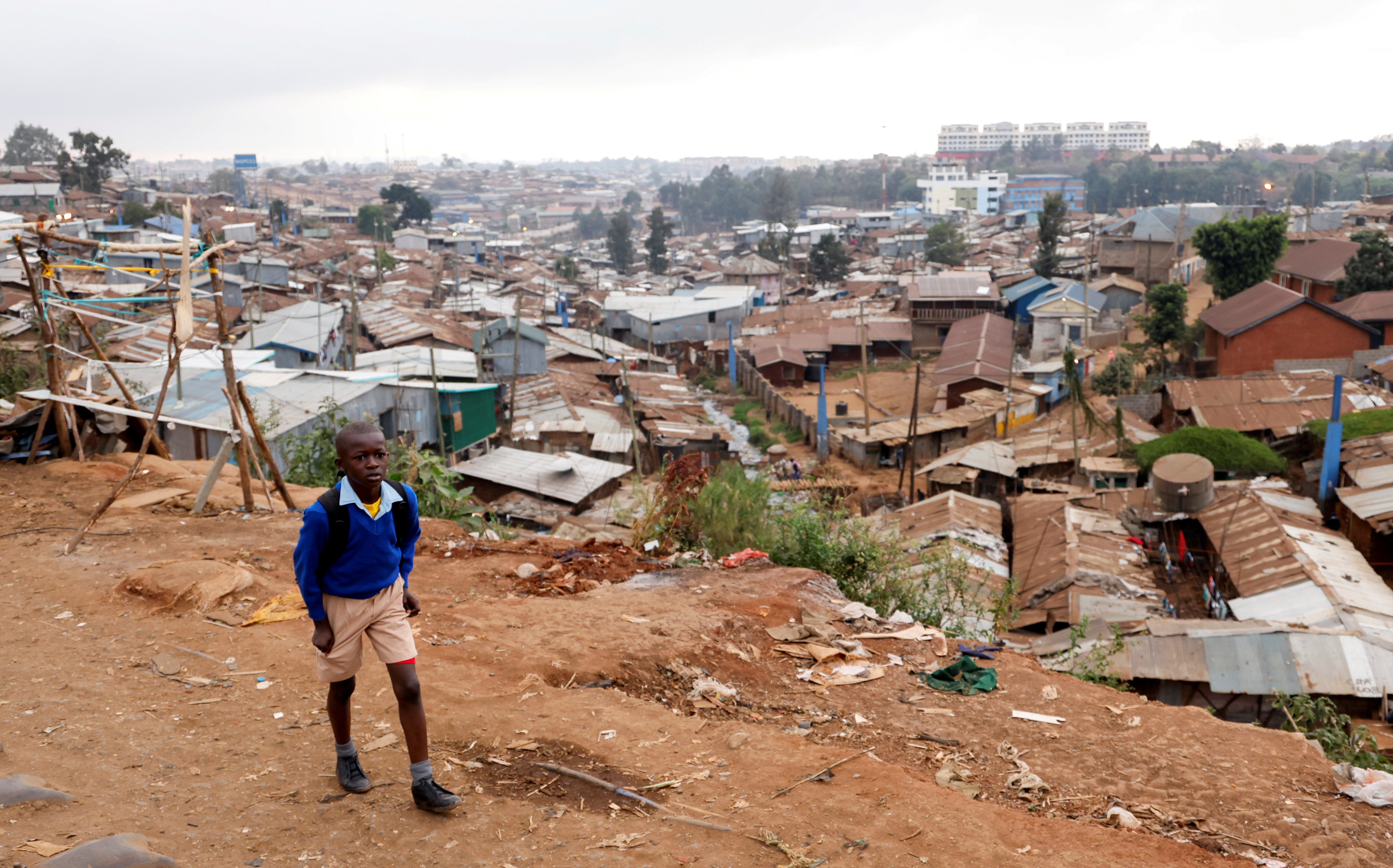 A schoolboy walks to school during the partial reopening of schools, after the government scrapped plans to cancel the academic year due to the coronavirus disease (COVID-19) pandemic, in Kibera slums of Nairobi, Kenya October 12, 2020.
