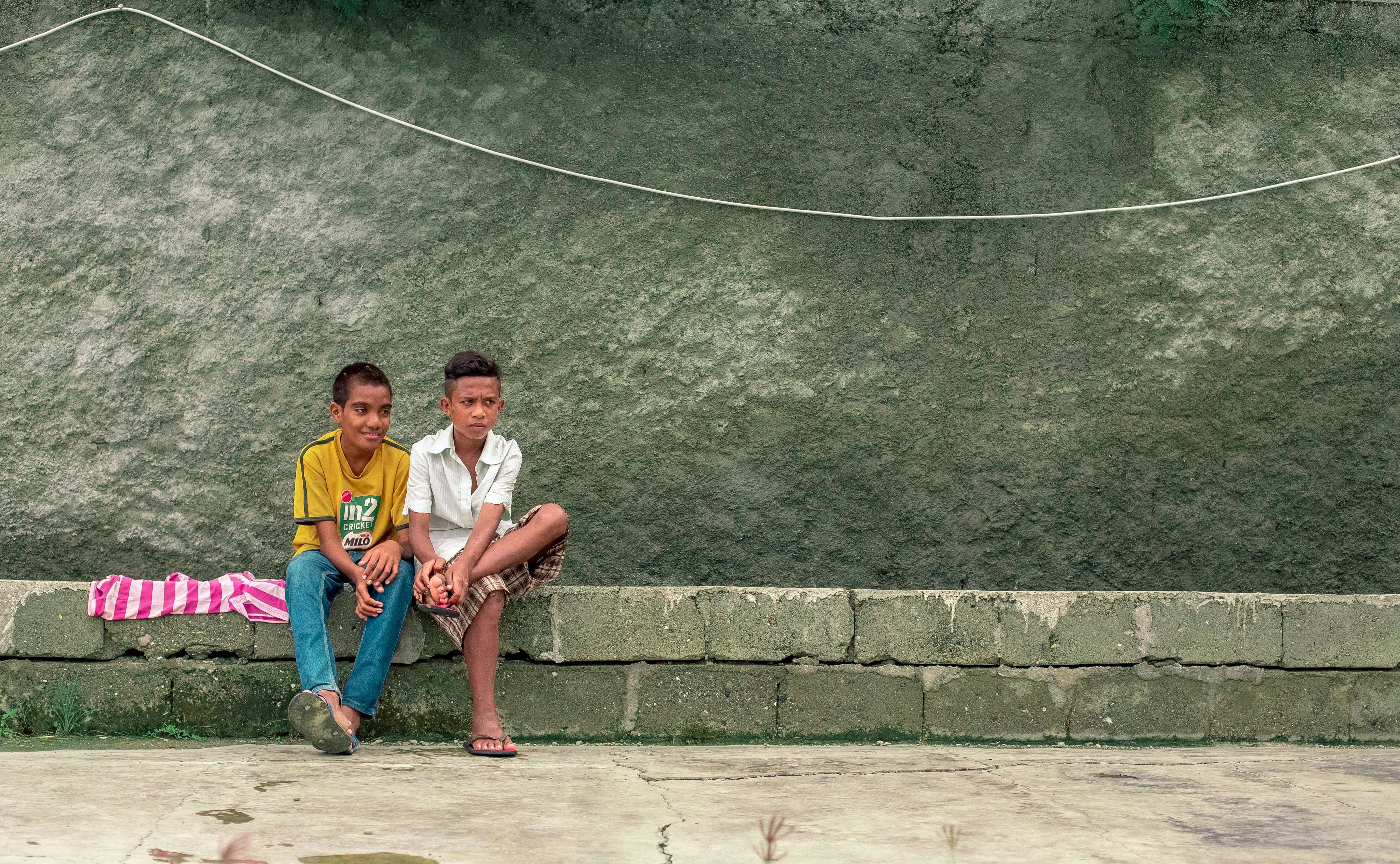 Two asian children sitting on a wall.