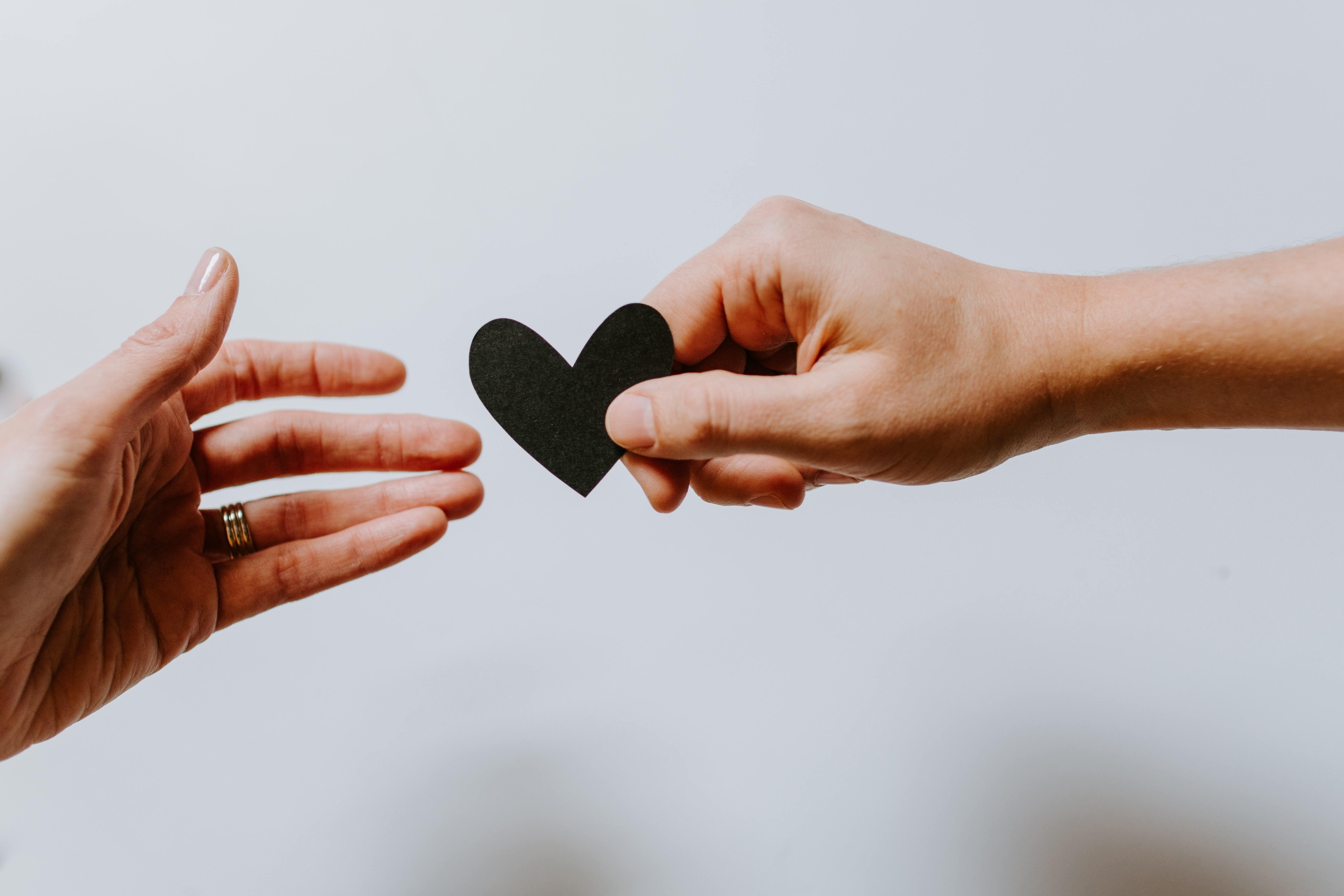A man handing a woman a paper heart