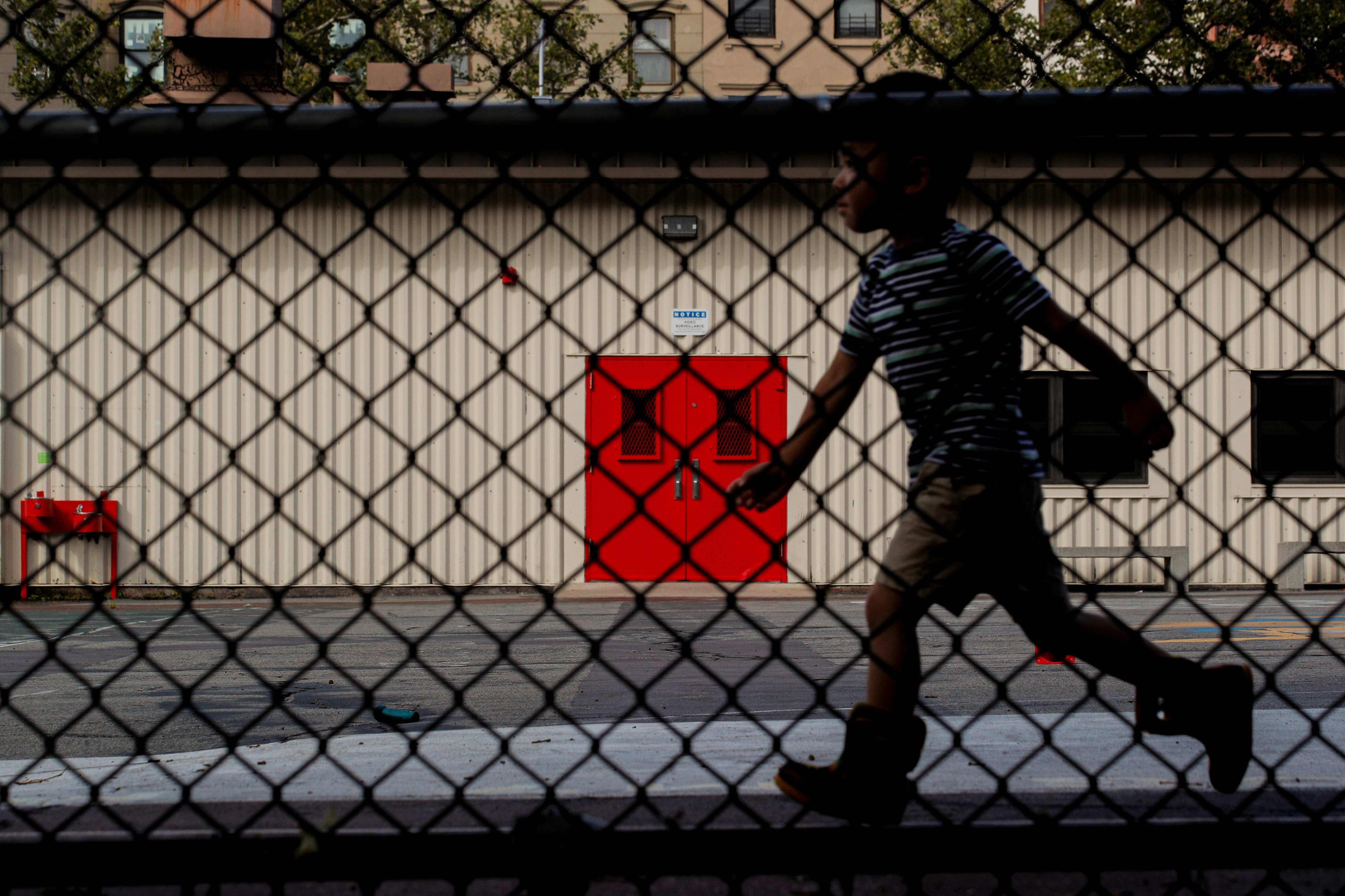 A child plays in the yard at New York Public School 321 in the Park Slope neighbourhood in Brooklyn, New York, U.S., August 7, 2020. REUTERS/Brendan McDermid - RC299I9N63ZA