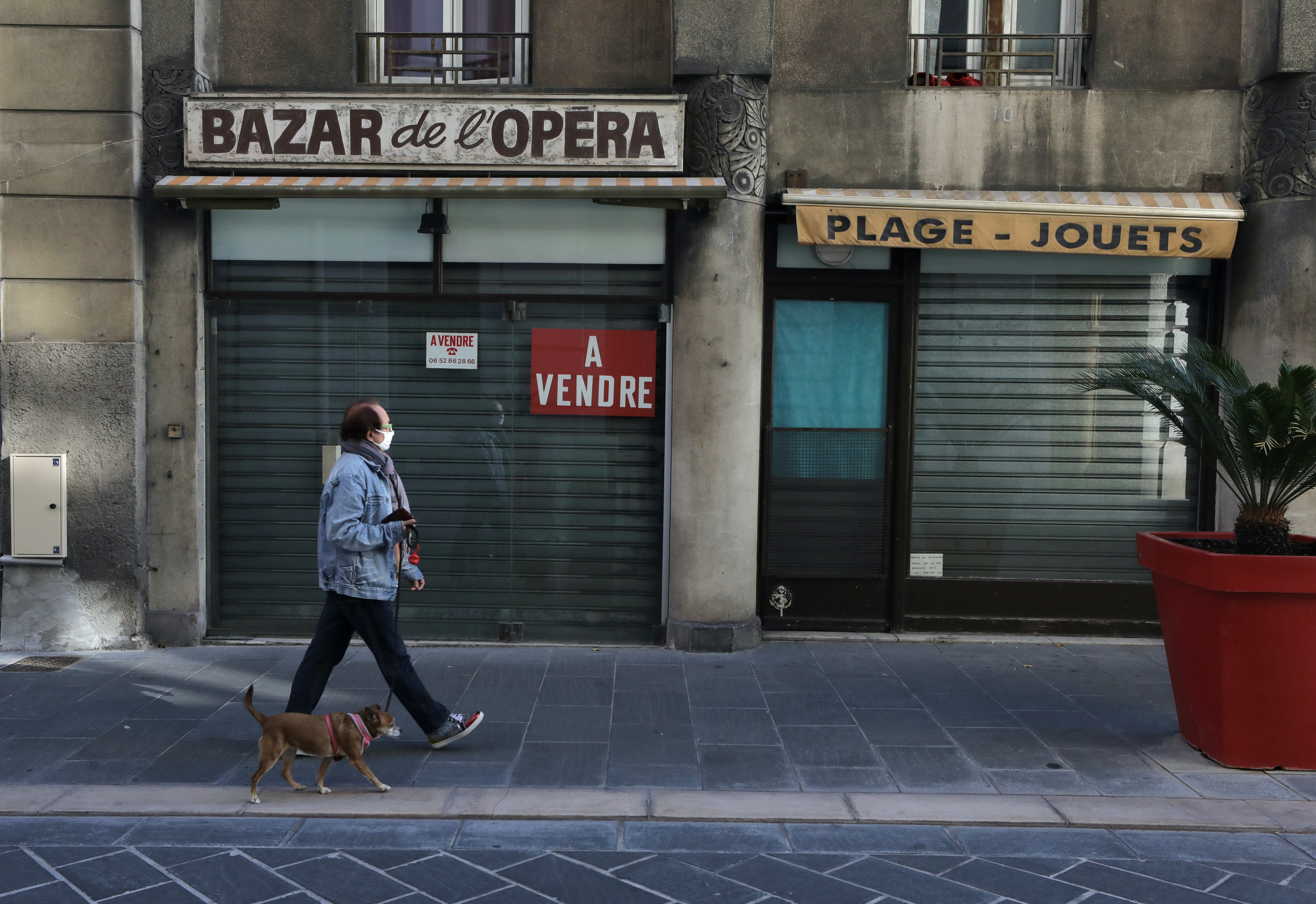 A woman walks his dog past a closed shop on sale during the second national lockdown as part of the measures to fight a second wave of the coronavirus disease (COVID-19) in Nice,France, November 17, 2020. REUTERS/EricGaillard - RC215K9SY6ZU