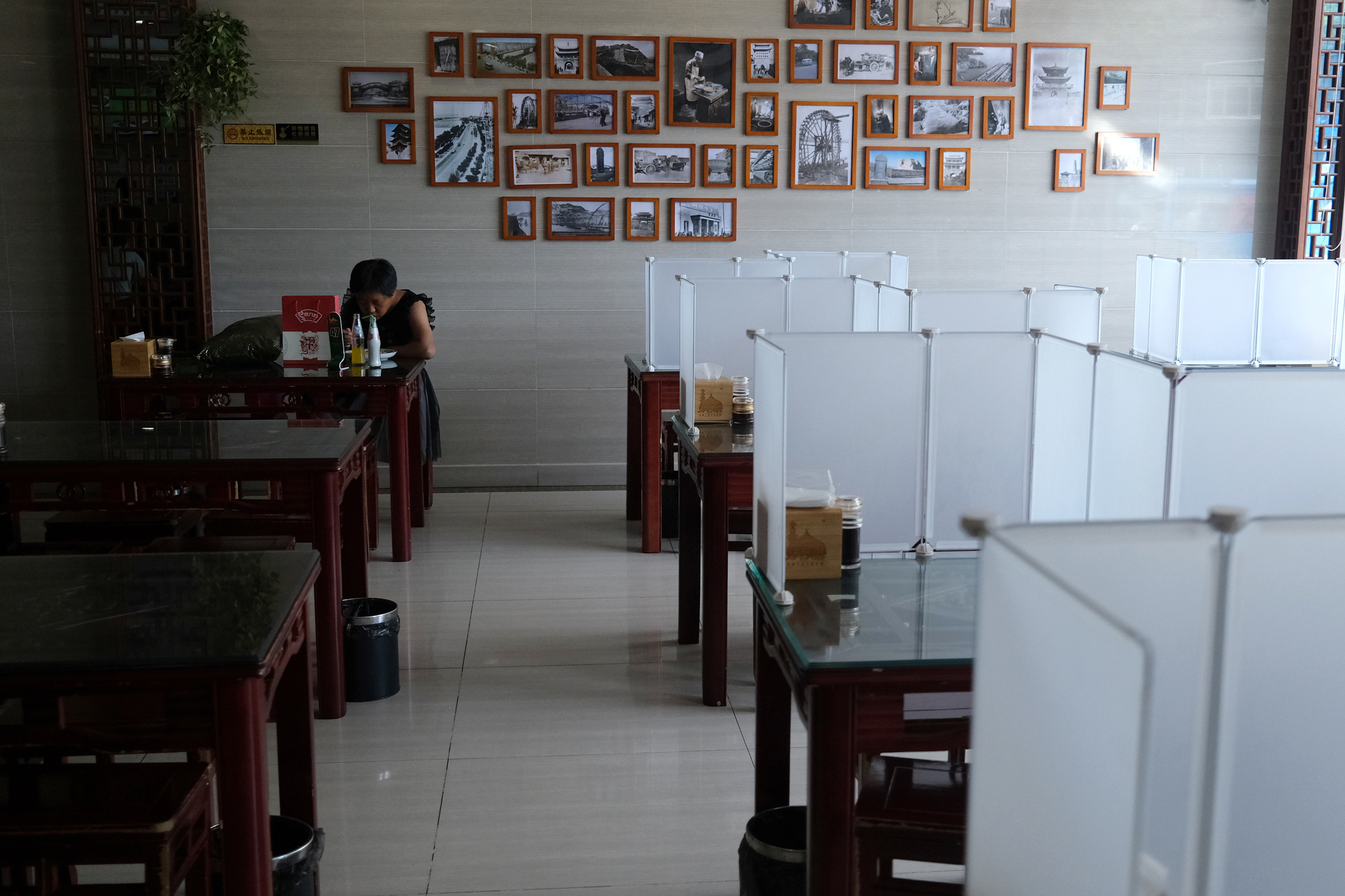 A customer eats meal next to tables with partitions, following the outbreak of the coronavirus disease (COVID-19), at a restaurant in Beijing, China June 30, 2020. REUTERS/Tingshu Wang - RC2FJH9EXEBB