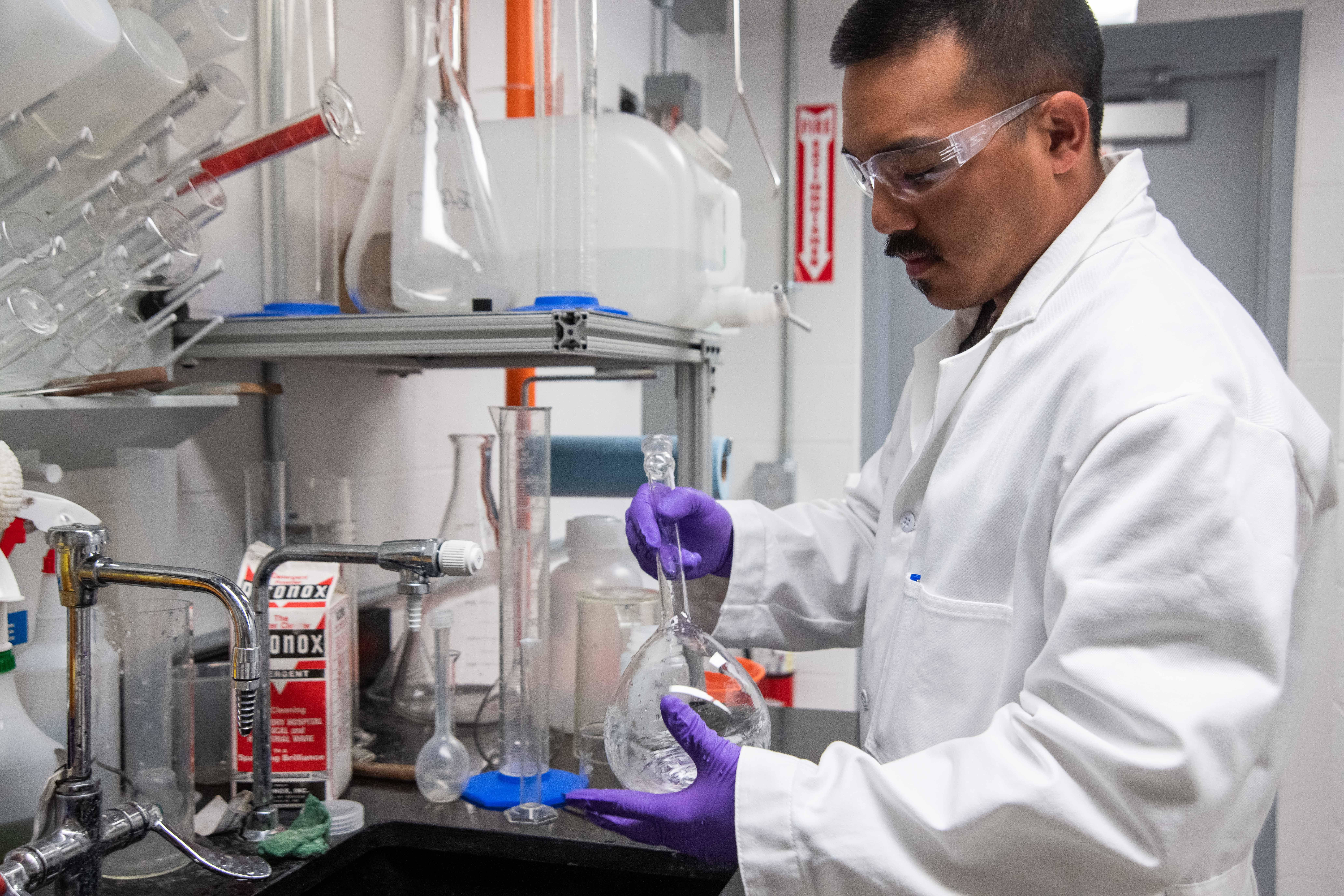 A scientist in a laboratory holding a flask