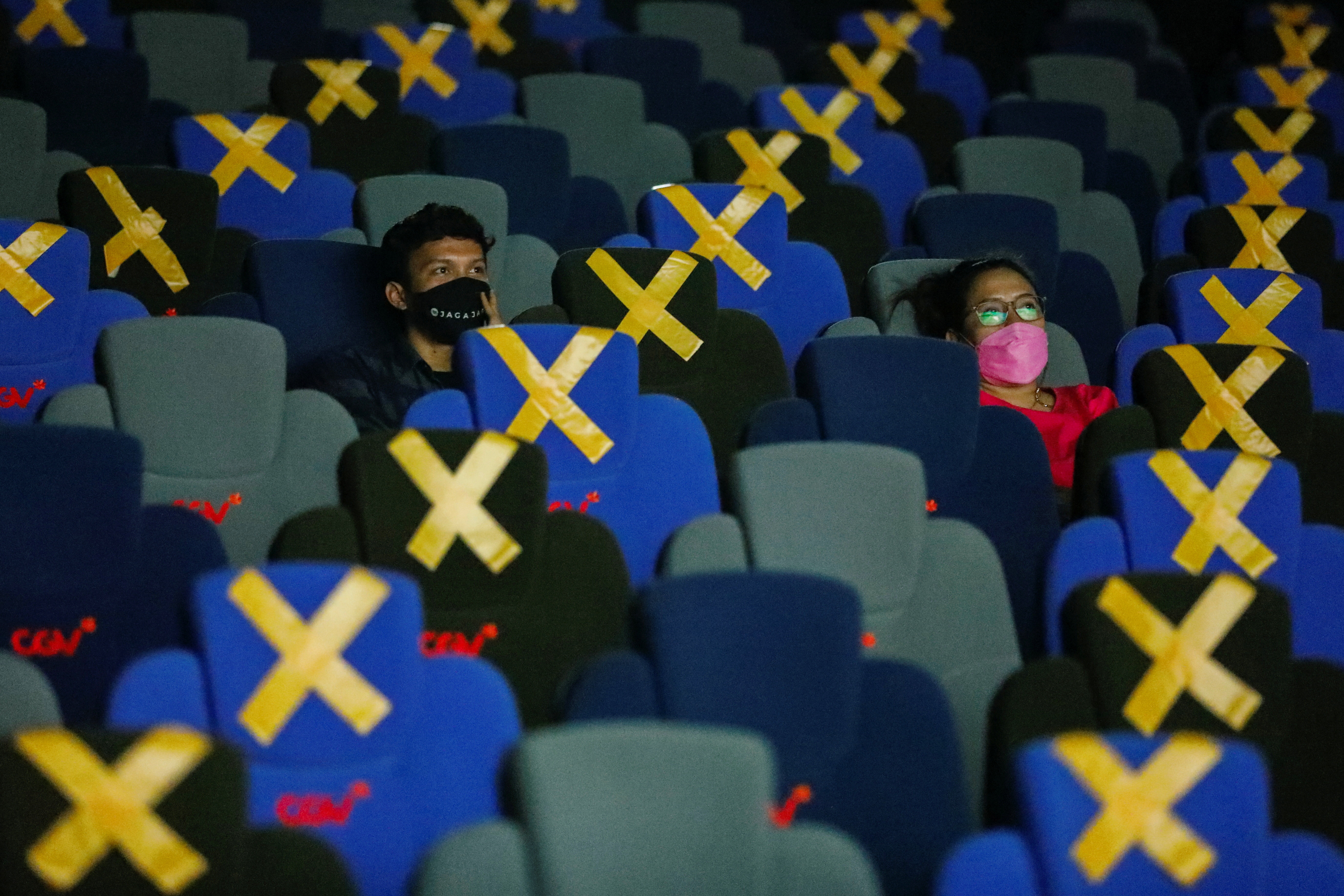 Visitors wearing protective masks watch a movie at a cinema as it is reopened after the ease of restrictions amid the coronavirus disease (COVID-19) pandemic in Jakarta, Indonesia, September 16, 2021. REUTERS/Willy Kurniawan - RC2VQP9LHOM0