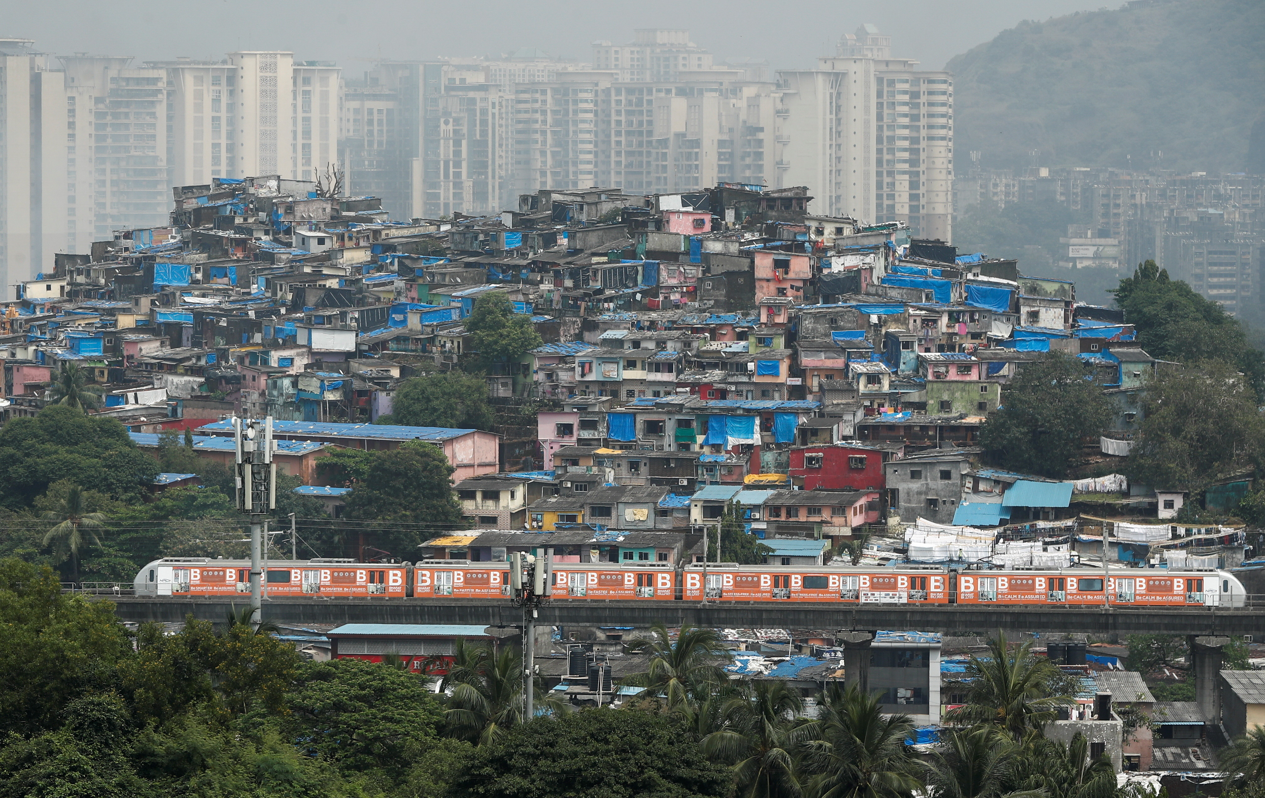 A metro train moves past slums and buildings after the restart of its operations, amidst the spread of the coronavirus disease (COVID-19), in Mumbai, India October 19, 2020