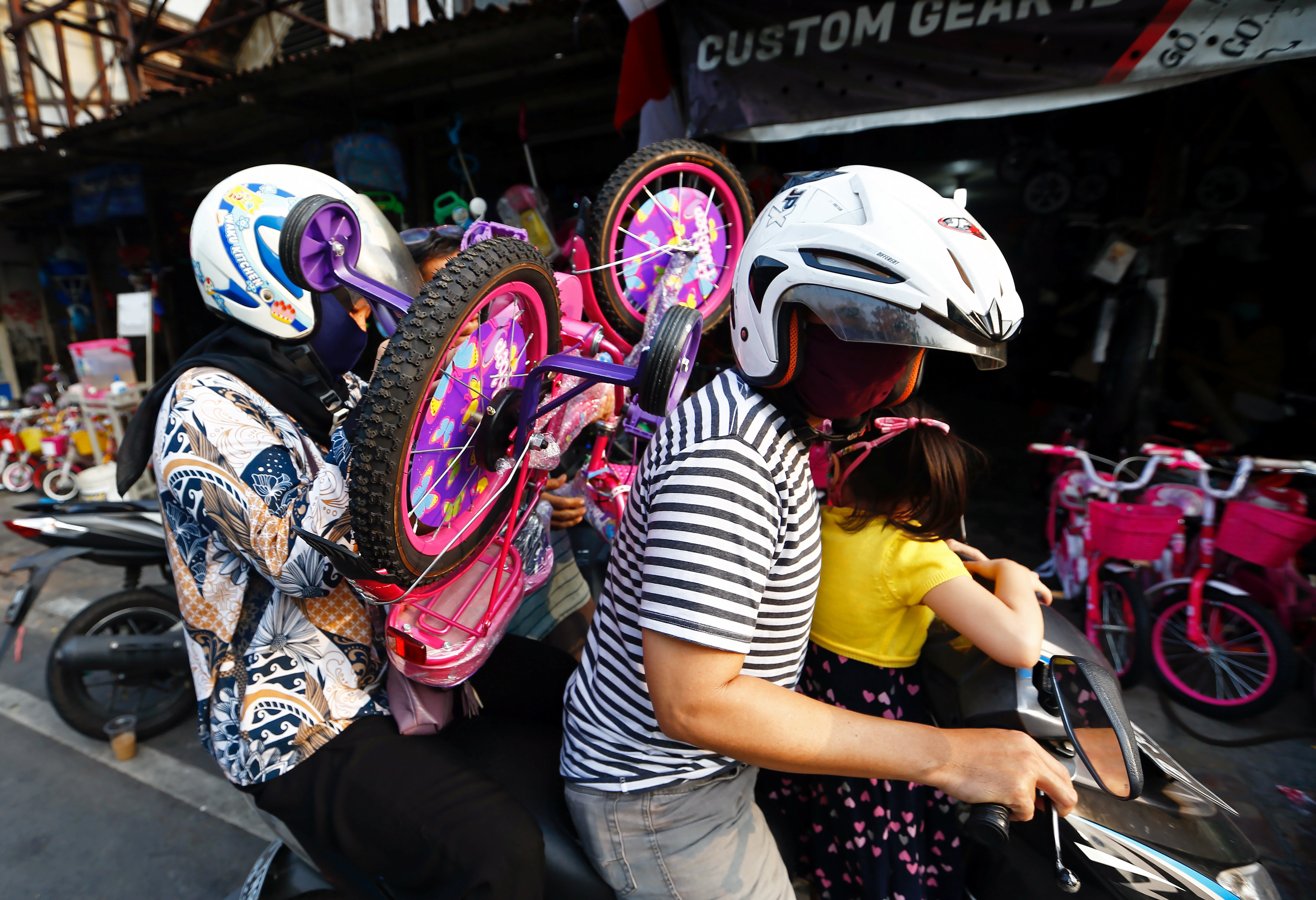 Customers wearing protective face masks carry a bicycle on a motorbike after shopping at a bicycle store, amid the coronavirus disease (COVID-19) outbreak in Jakarta, Indonesia, August 8, 2020. REUTERS/Ajeng Dinar Ulfiana - RC2N9I9I0AA8