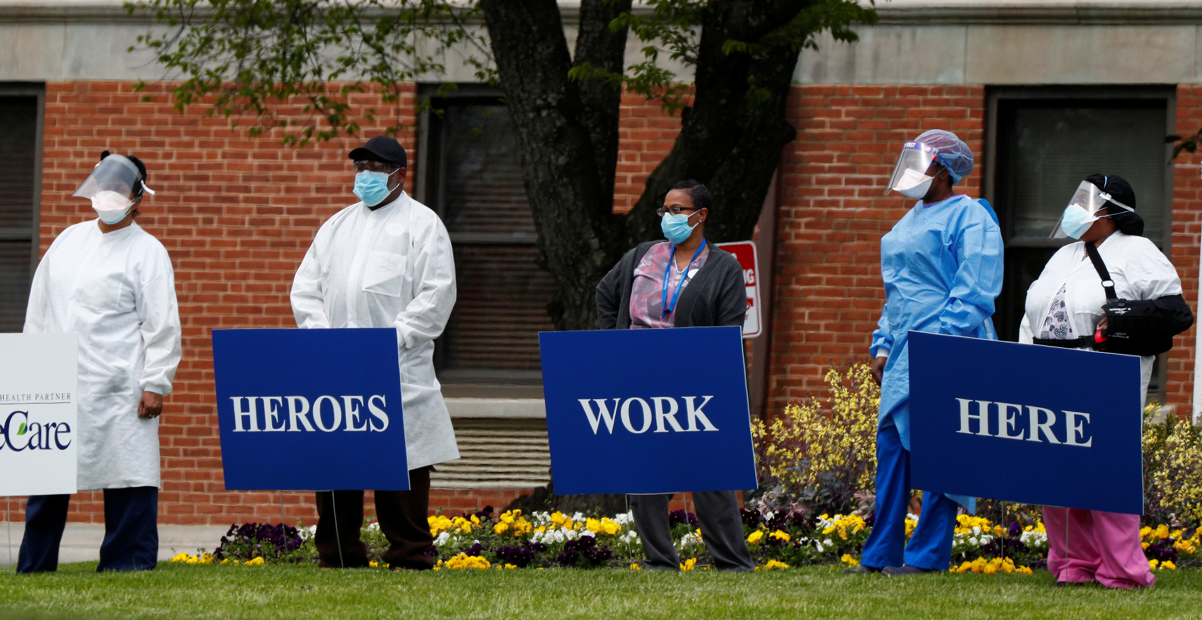 """Medical workers pose for photos taken by coworkers as they stand with signs saying """"Heroes Work Here"""" that have been placed outside the FutureCare Lochearn senior nursing facility where a large number of residents and staff have reportedly tested positive following a coronavirus (COVID-19) disease outbreak at the facility in Baltimore, Maryland, U.S. April 17, 2020."""