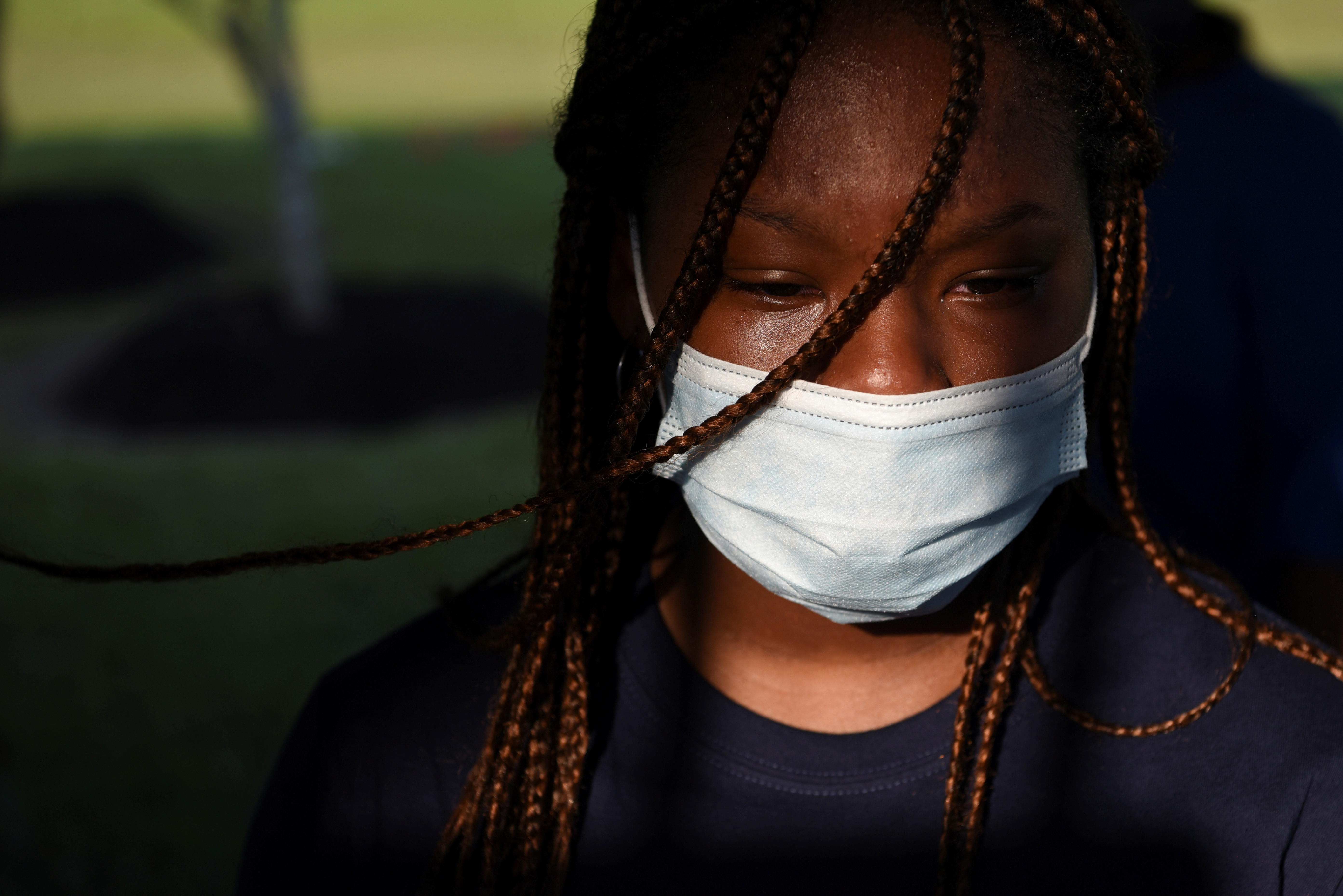A young woman sheds a tear as people visit the gravesite of George Floyd, whose death in Minneapolis police custody has sparked nationwide protests against racial inequality, in Pearland, Texas, U.S., June 9, 2020. REUTERS/Callaghan O'Hare - RC216H97NFT4