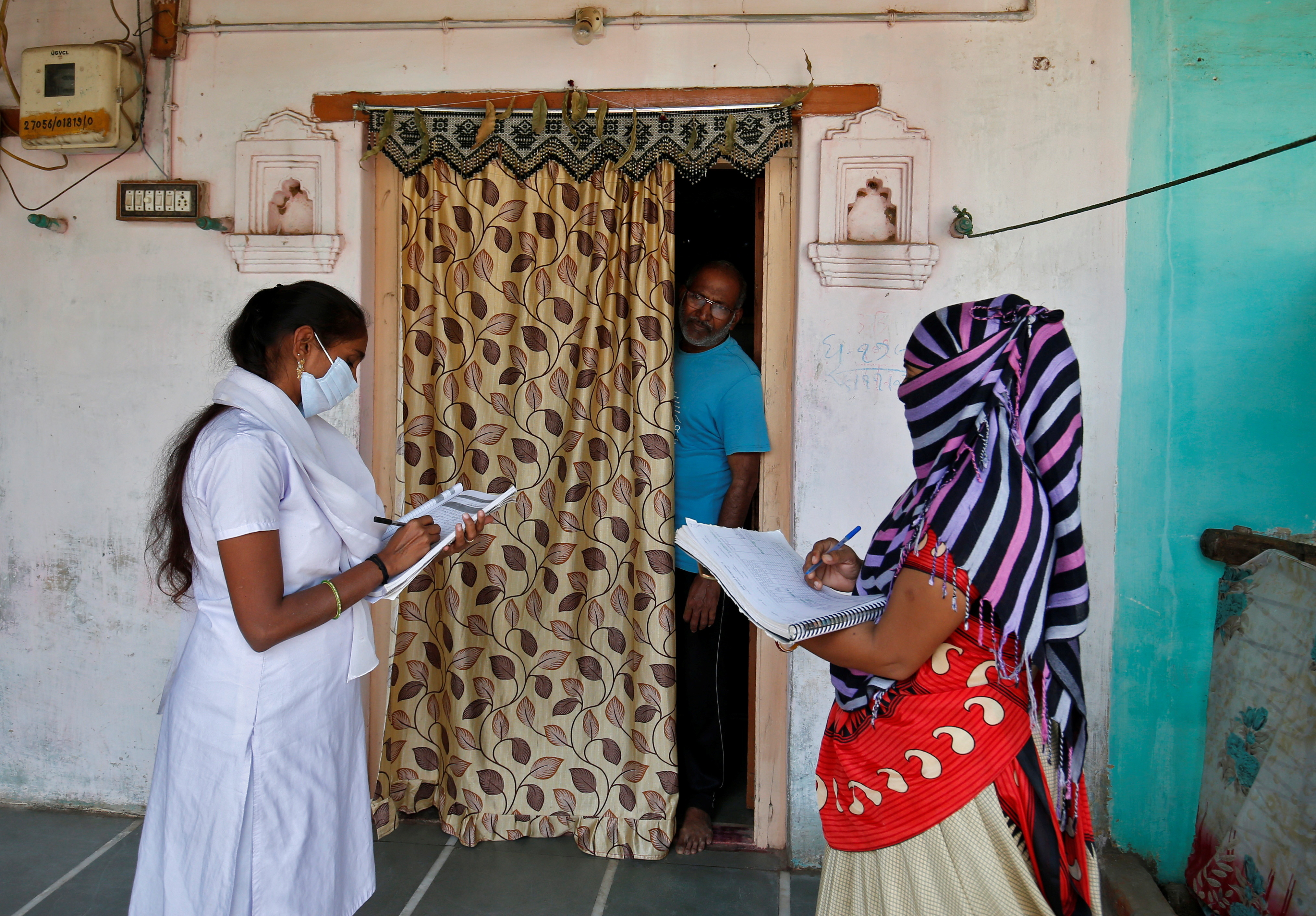 Health workers collect personal data from a man as they prepare a list during a door-to-door survey for the first shot of COVID-19 vaccine for people above 50 years of age and those with comorbidities, in a village on the outskirts of Ahmedabad, India, December 14, 2020. REUTERS/Amit Dave - RC21NK9S3WNP