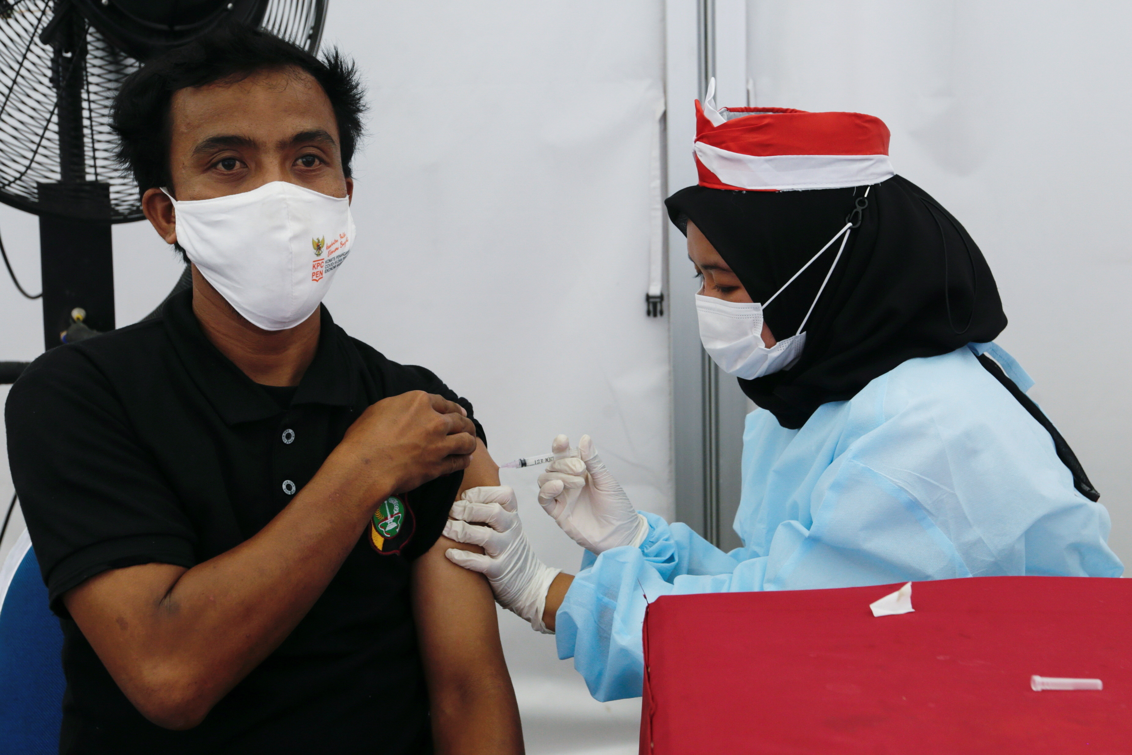 A man receives a dose of a vaccine against the coronavirus disease (COVID-19) during a vaccination program in Jakarta, Indonesia, August 16, 2021.