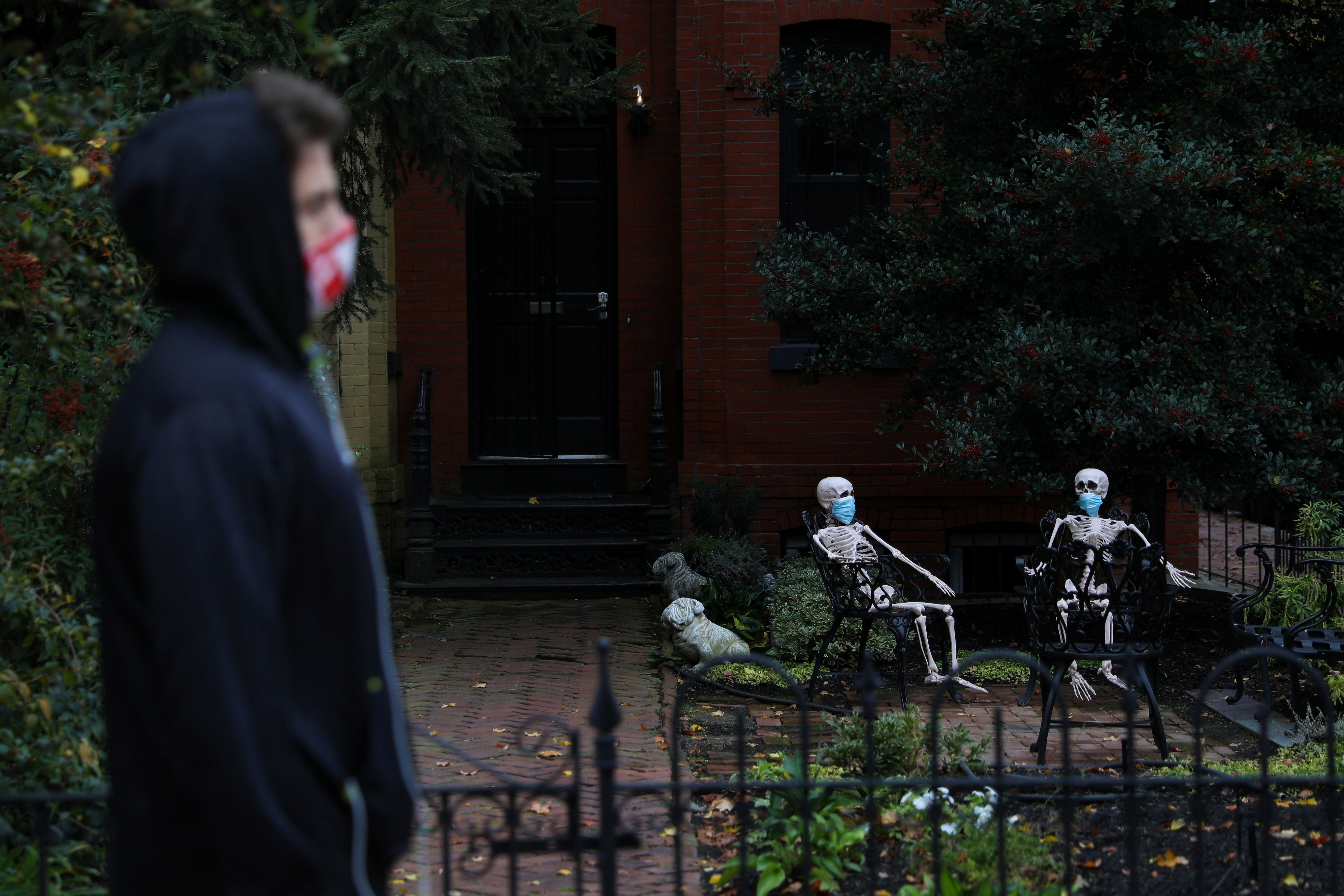 Decorative Halloween skeletons wearing protective face masks are seen along 16th Street, amid the coronavirus disease (COVID-19) outbreak, in Washington, U.S., October 28, 2020. REUTERS/Tom Brenner - RC2URJ9W32NQ