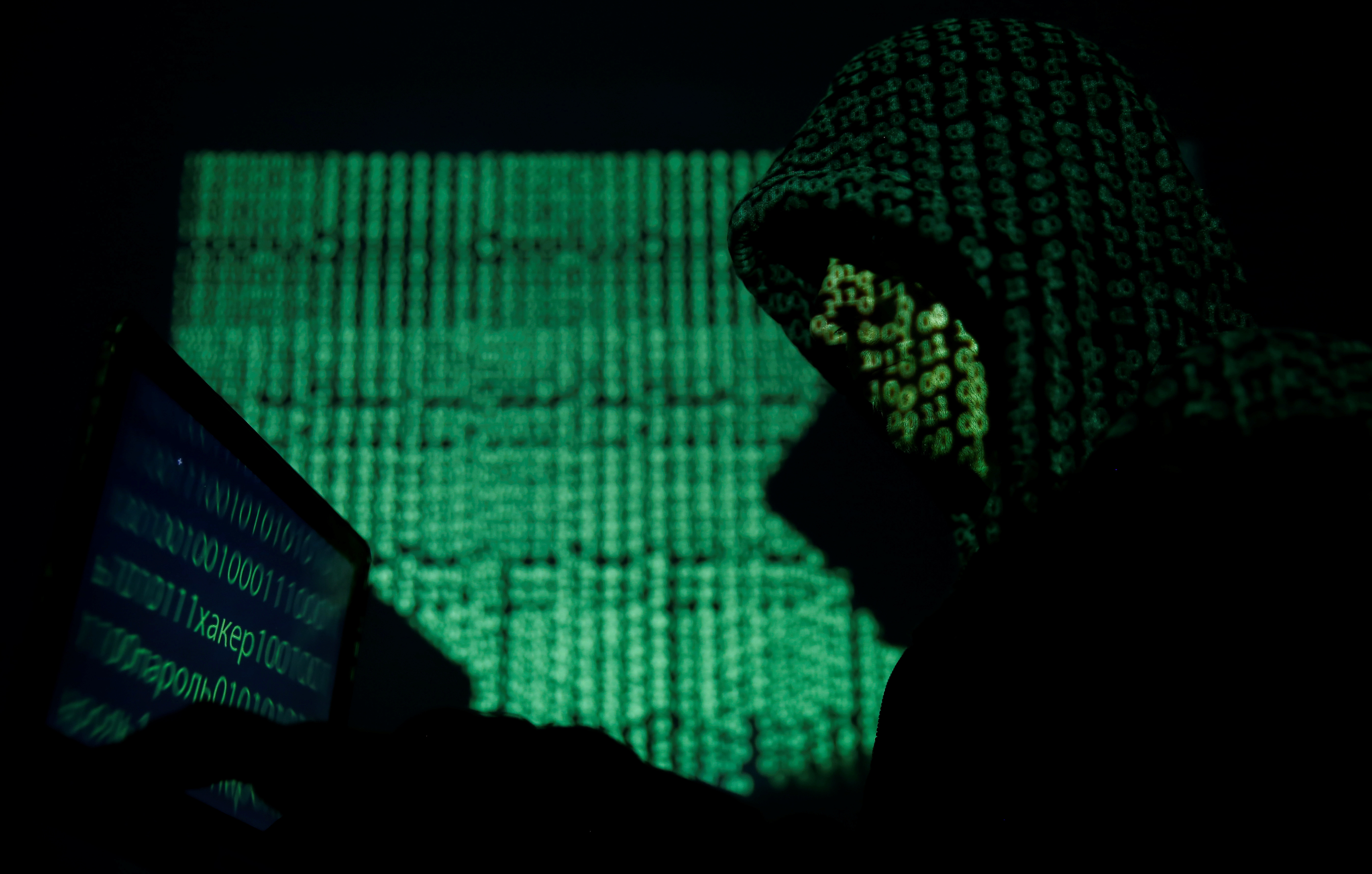A hooded man holds a laptop computer as cyber code is projected on him in this illustration picture taken on May 13, 2017. REUTERS/Kacper Pempel/Illustration - RC14A7592410
