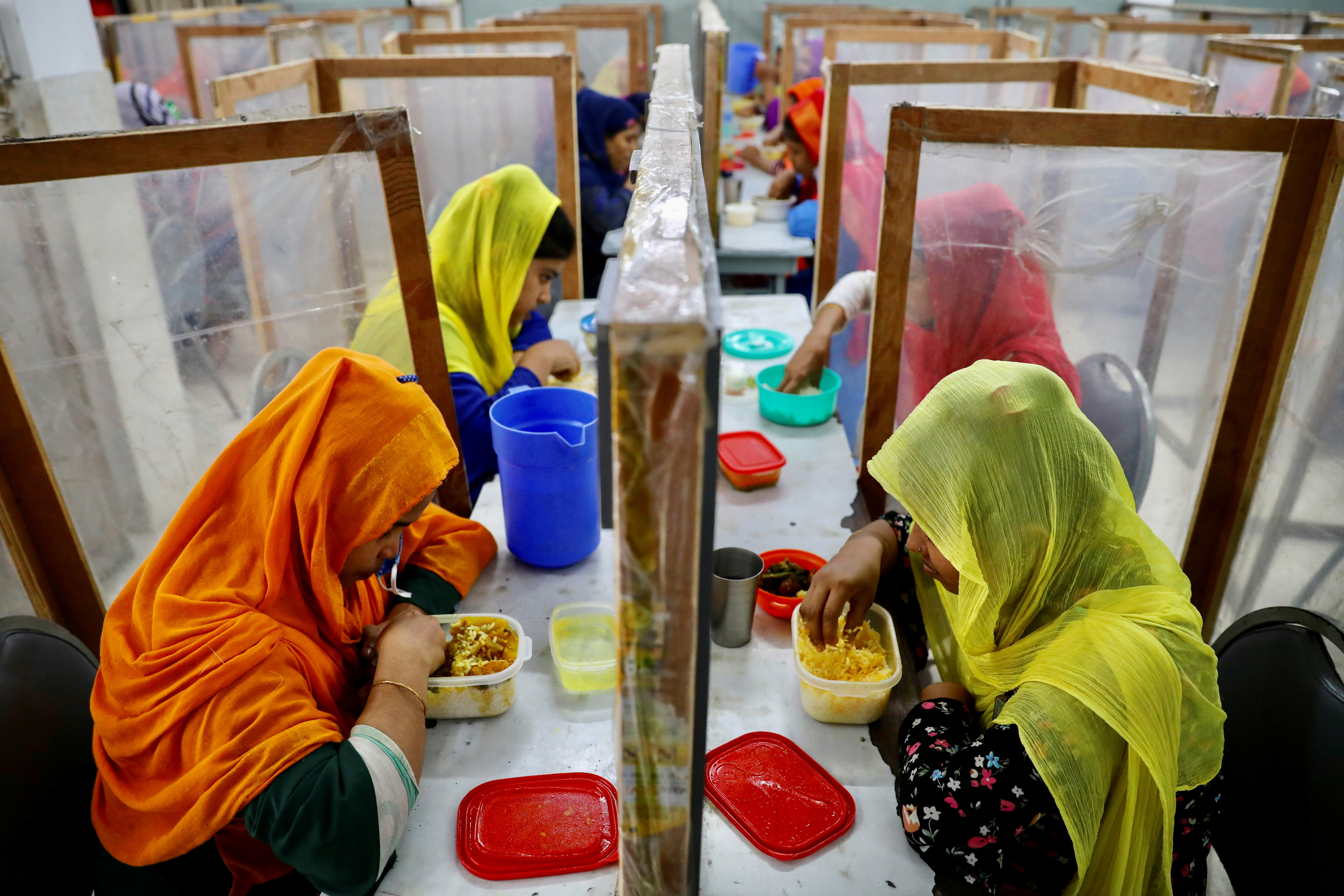 Employees dine between polythene sheets, as a safety measure to reduce the spread of coronavirus disease (COVID-19), at The Civil Engineering Limited garment factory in Dhaka, Bangladesh, August 17, 2021. REUTERS/Mohammad Ponir Hossain     TPX IMAGES OF THE DAY - RC2V6P905VP9