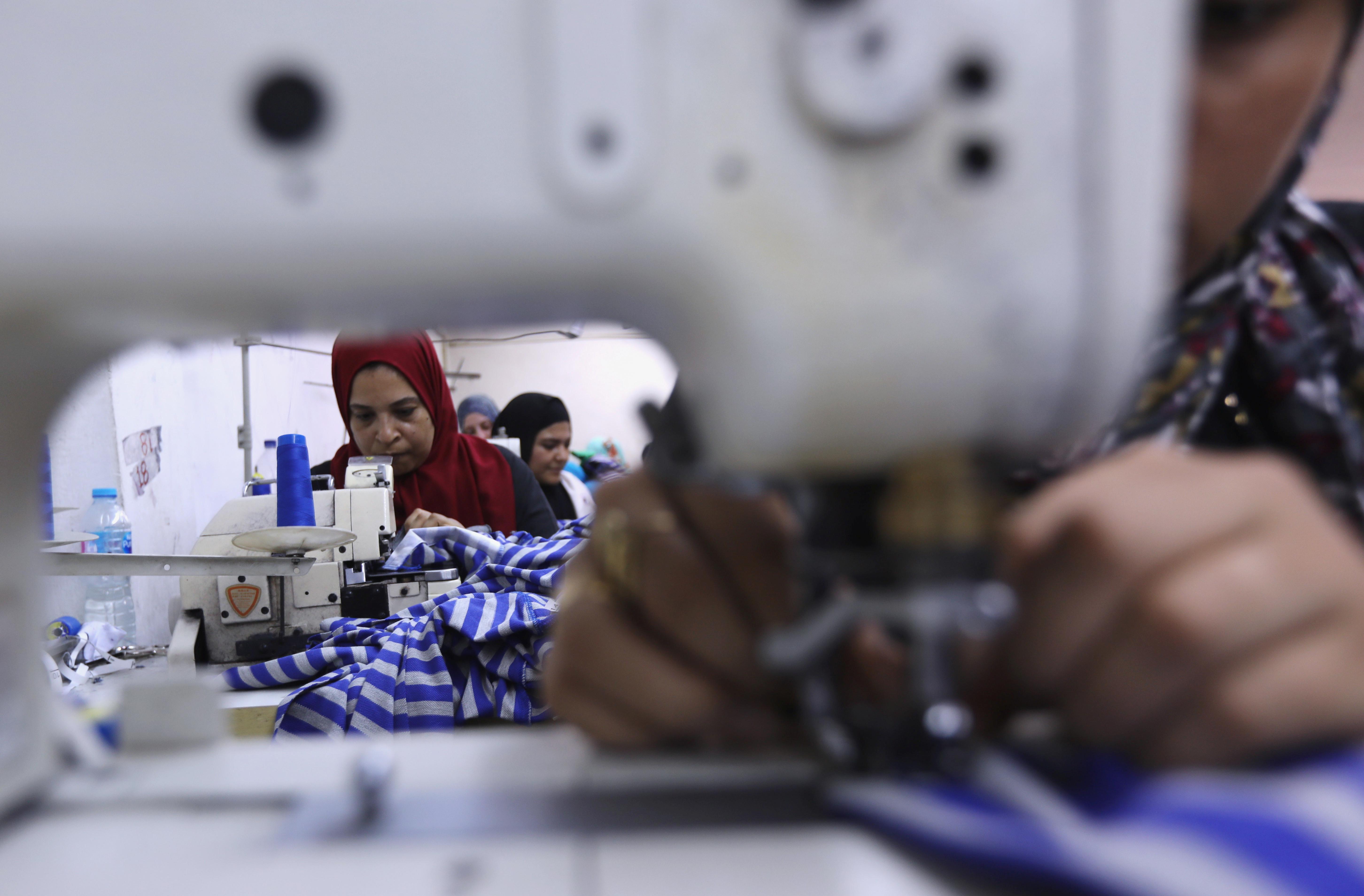 Egyptian women work as they sew school uniform inside a factory