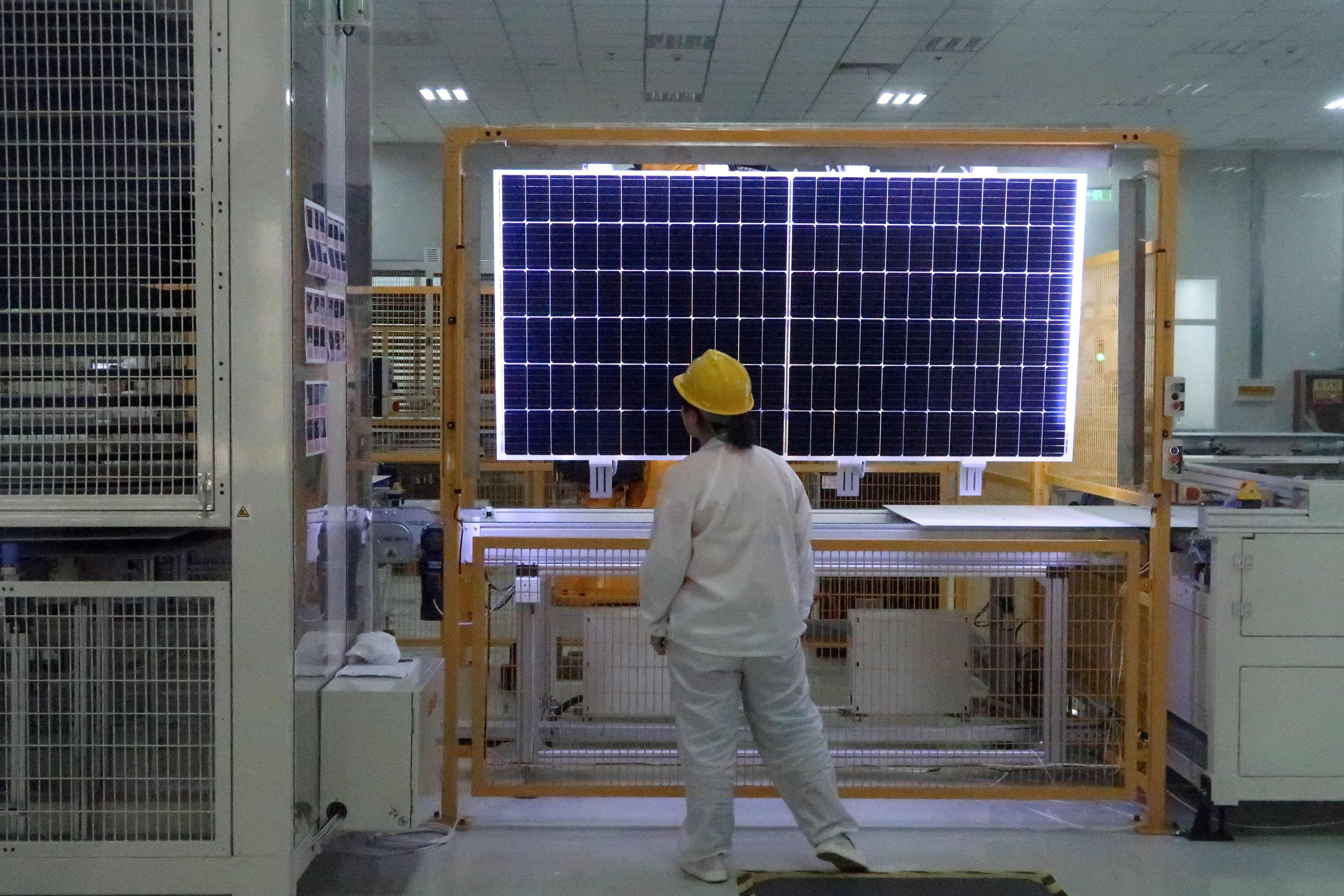 A worker conducts quality-check of a solar module product at a factory of a monocrystalline silicon solar equipment manufacturer LONGi Green Technology Co, in Xian, Shaanxi province, China December 10, 2019. Picture taken December 10, 2019. REUTERS/Muyu Xu - RC2JXD9MAGM8