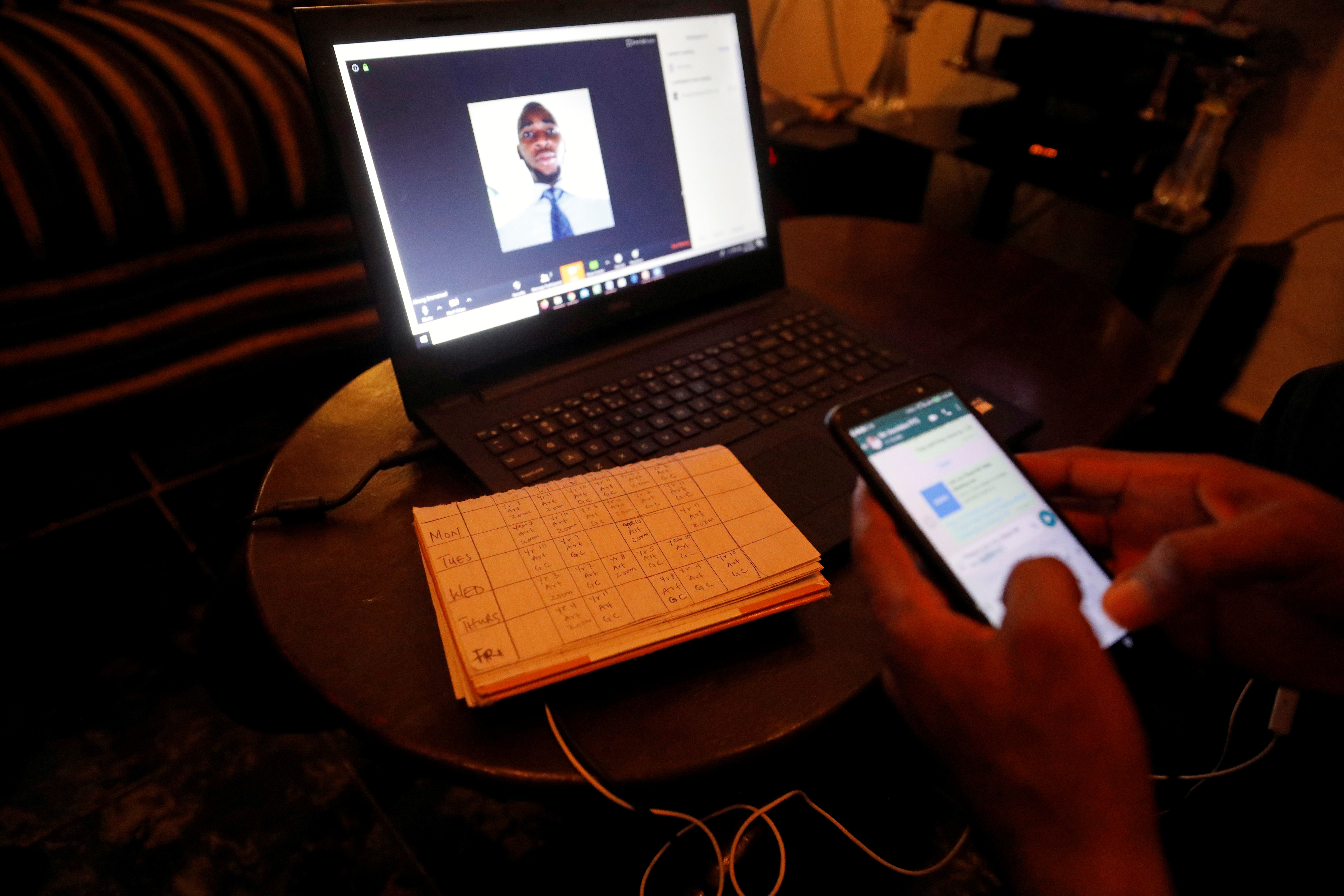 Nigerian teacher, Emmanuel Ntaji, types on his phone as he awaits his students to come online on the Zoom app for their e-learning class, at his home during a lockdown imposed by the authorities to limit the spread of the coronavirus disease (COVID-19) in Lagos, Nigeria April 23, 2020. Picture taken April 23, 2020. REUTERS/Temilade Adelaja - RC2NFG90ZJ4L