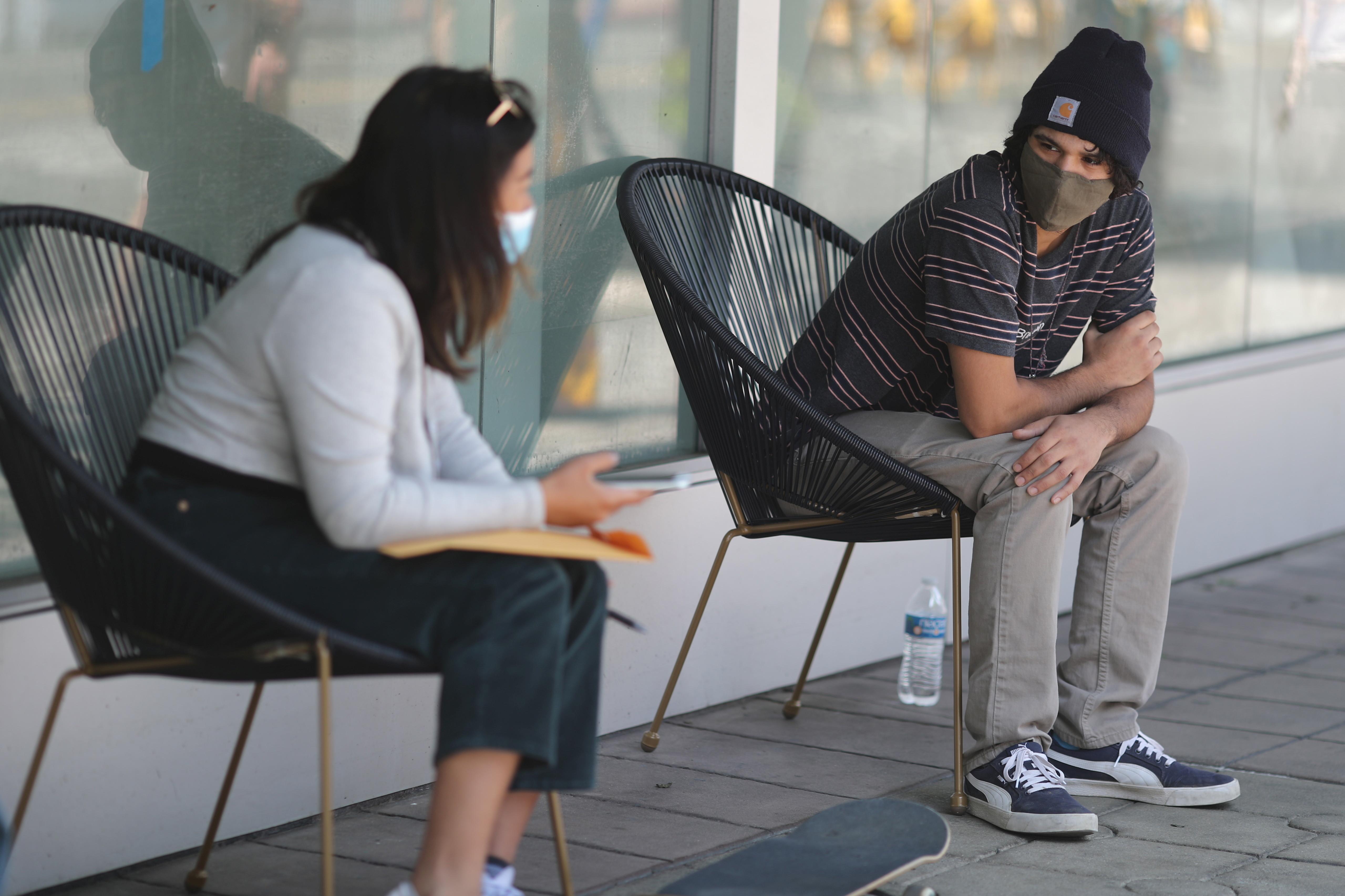 two people in face maks sit outside socially sitanced
