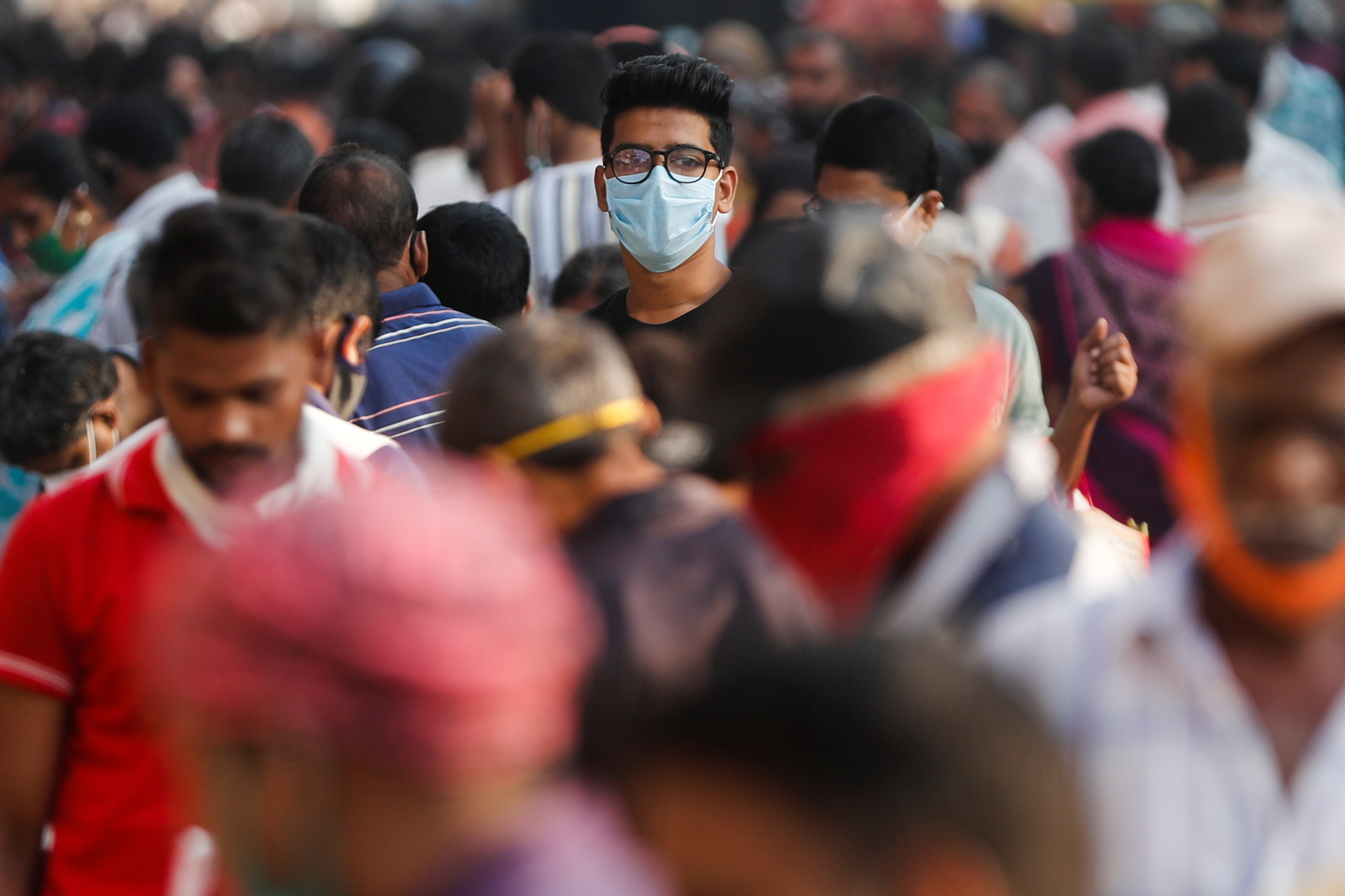 A man wearing a protective mask is seen among people at a crowded market amidst the spread of the coronavirus disease (COVID-19) in Mumbai, India, October 29, 2020. REUTERS/Francis Mascarenhas - RC24SJ9M7M7C