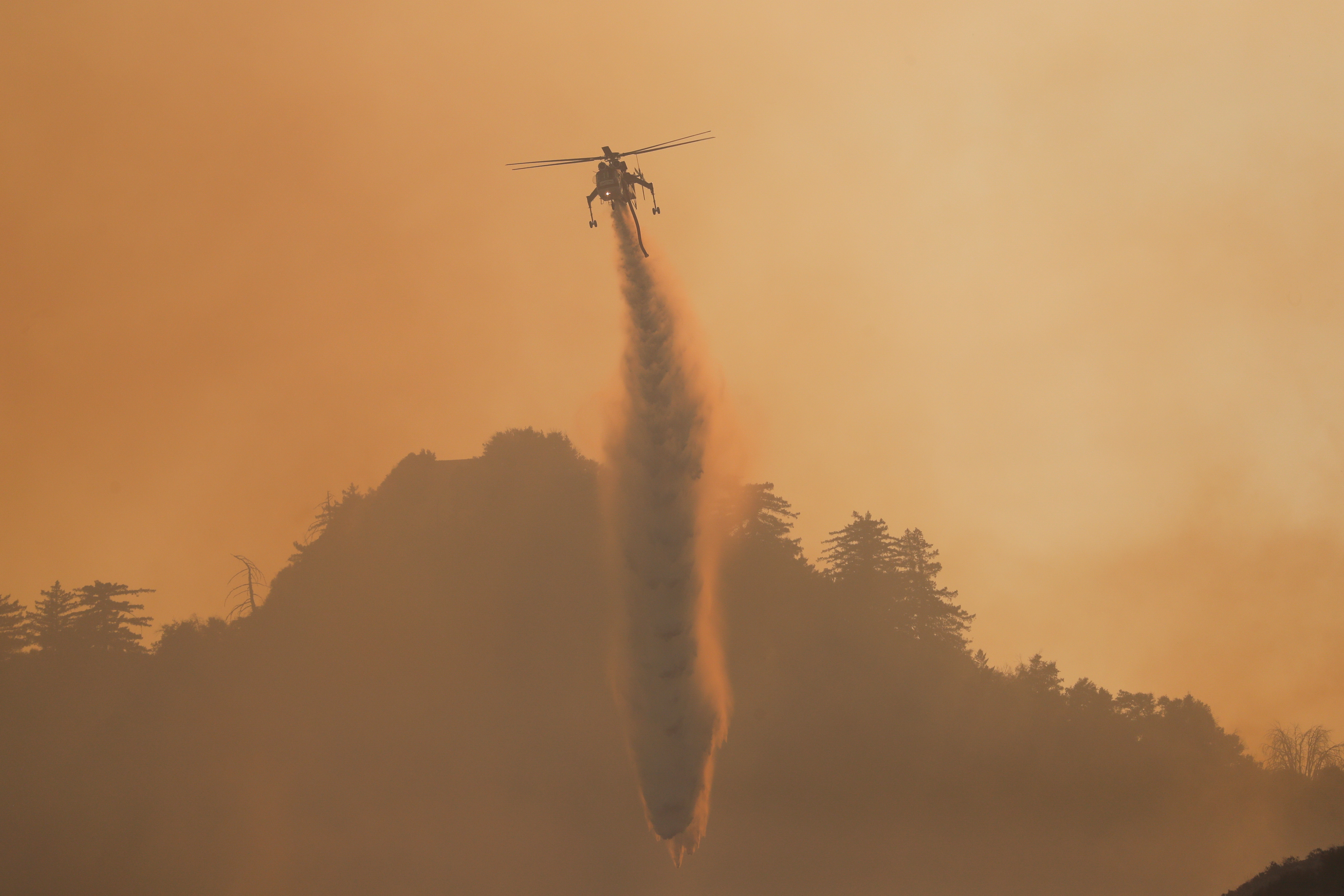 A helicopter makes a water drop over the Bobcat Fire burning near Mount Wilson in the Angeles National Forest, near Los Angeles, U.S., September 23, 2020. REUTERS/Mario Anzuoni - RC2Q4J91JM55