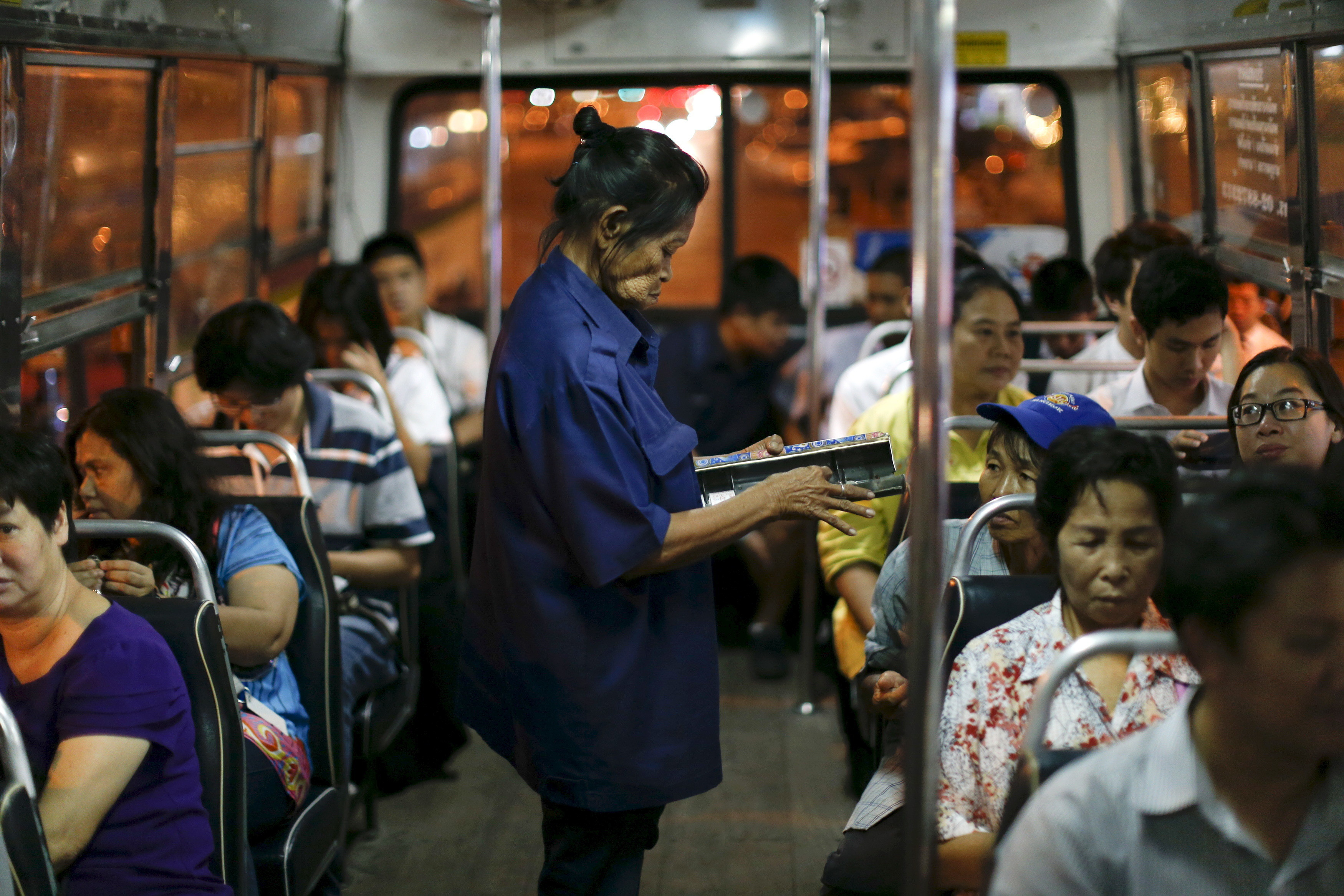 Pranom Chartyothin, a 72-year-old bus conductor, sells and collects bus tickets in downtown Bangkok, Thailand, February 3, 2016. Such scenes will only become more common in Thailand as its population rapidly ages, unlike its neighbours with more youthful populations. The World Bank estimates the working-age population will shrink by 11 percent by 2040, the fastest contraction among Southeast Asia's developing countries. Thailand's stage of economic development, the rising cost of living and education, and a population waiting longer to get married are among the reasons it is ageing more quickly than its neighbours. An effective contraception programme in the 1970s also played a part, said Sutayut Osornprasop, a human development specialist at the World Bank in Thailand.  Picture taken February 3, 2016. REUTERS/Jorge Silva       TPX IMAGES OF THE DAY      - GF10000302961