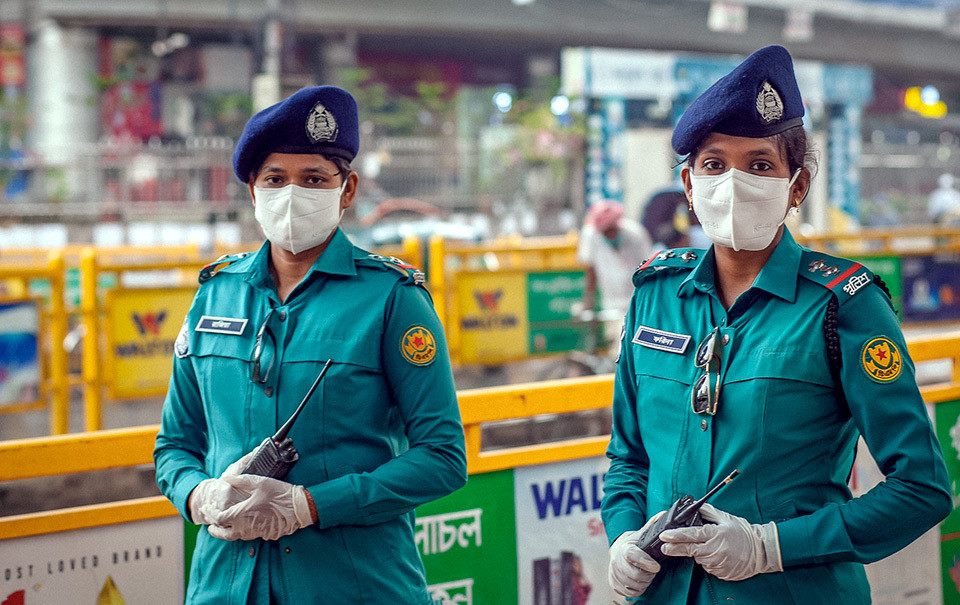 Two female police officers of Dhaka Metropolitan Police patrolling streets in Dhaka, Bangladesh. The visible presence of female police officers makes women feel safer