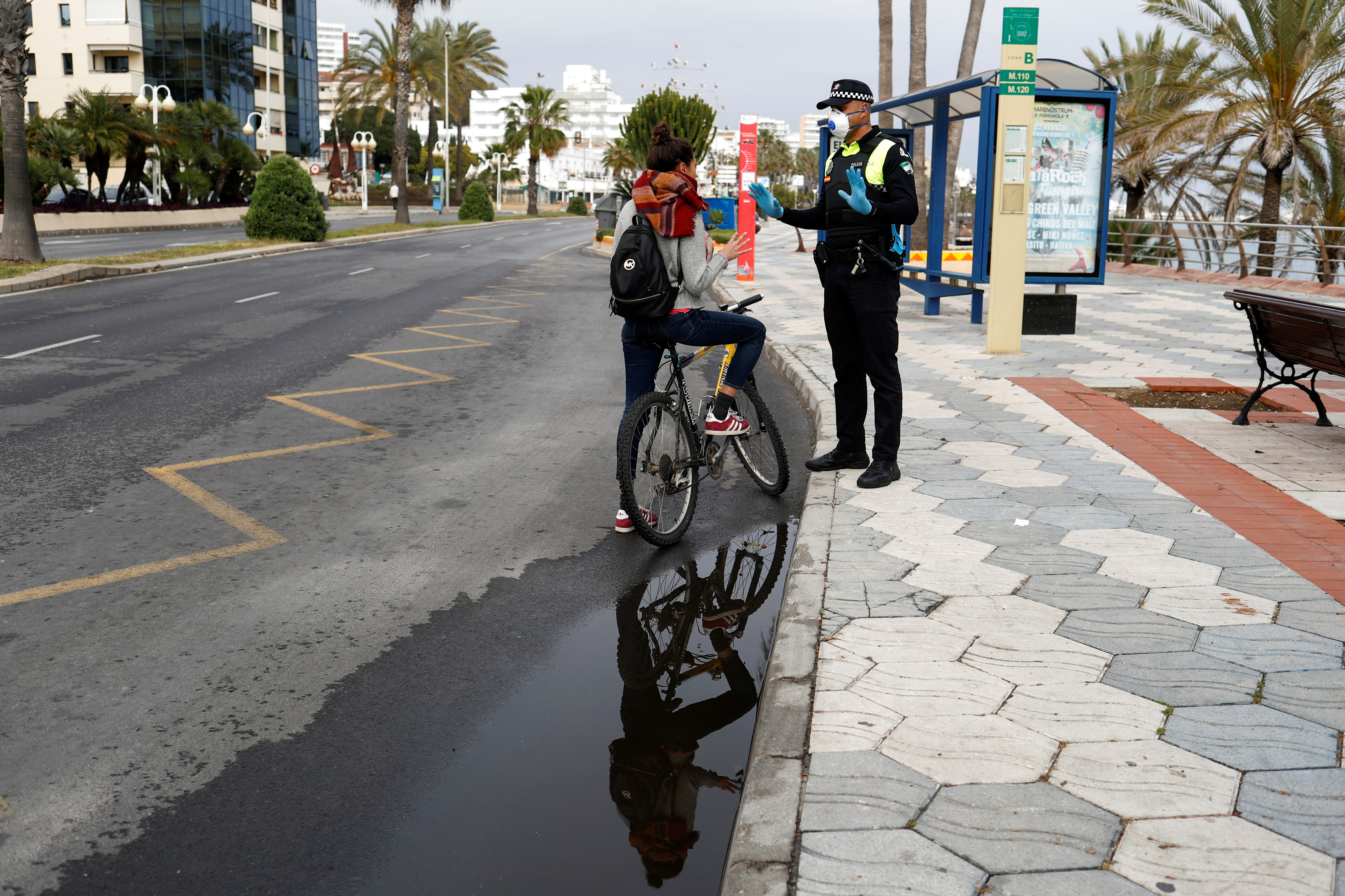 Rebecca Testa, 30, from Italy, asks a police officer if she can go back to Italy by car after she lost her job in Spain, during a partial lockdown as part of a 15-day state of emergency to combat the coronavirus outbreak in Benalmadena, on Costa del Sol, southern Spain, March 15, 2020.