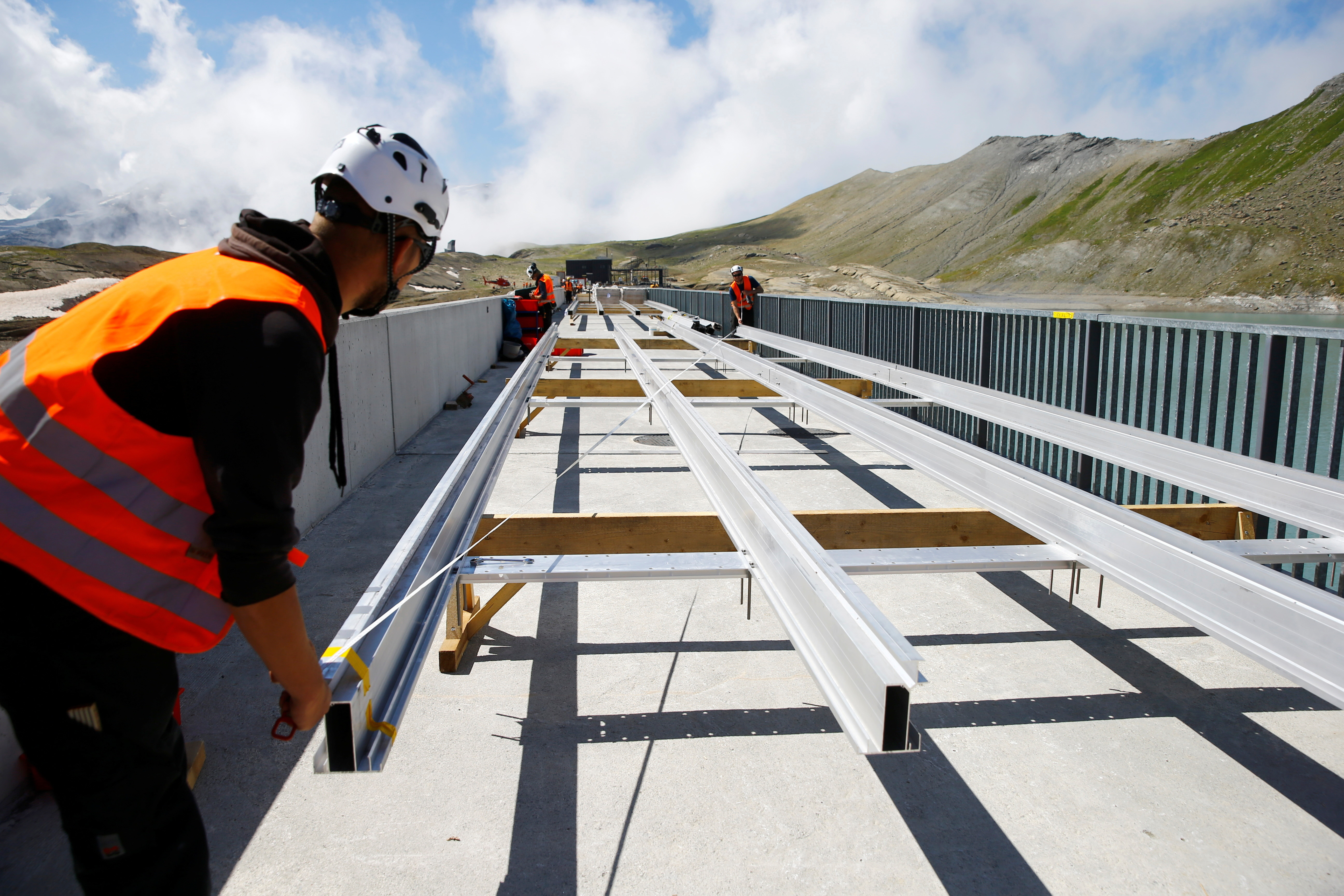 Workers measure a suspension for solar panels at the construction site of a large-scale photovoltaic system of Swiss energy provider Axpo at some 2500 metres above sea level on the dam of Lake Muttsee, Switzerland August 19, 2021. Picture taken August 19, 2021.   REUTERS/Arnd Wiegmann - RC2D8P9NFNZ1