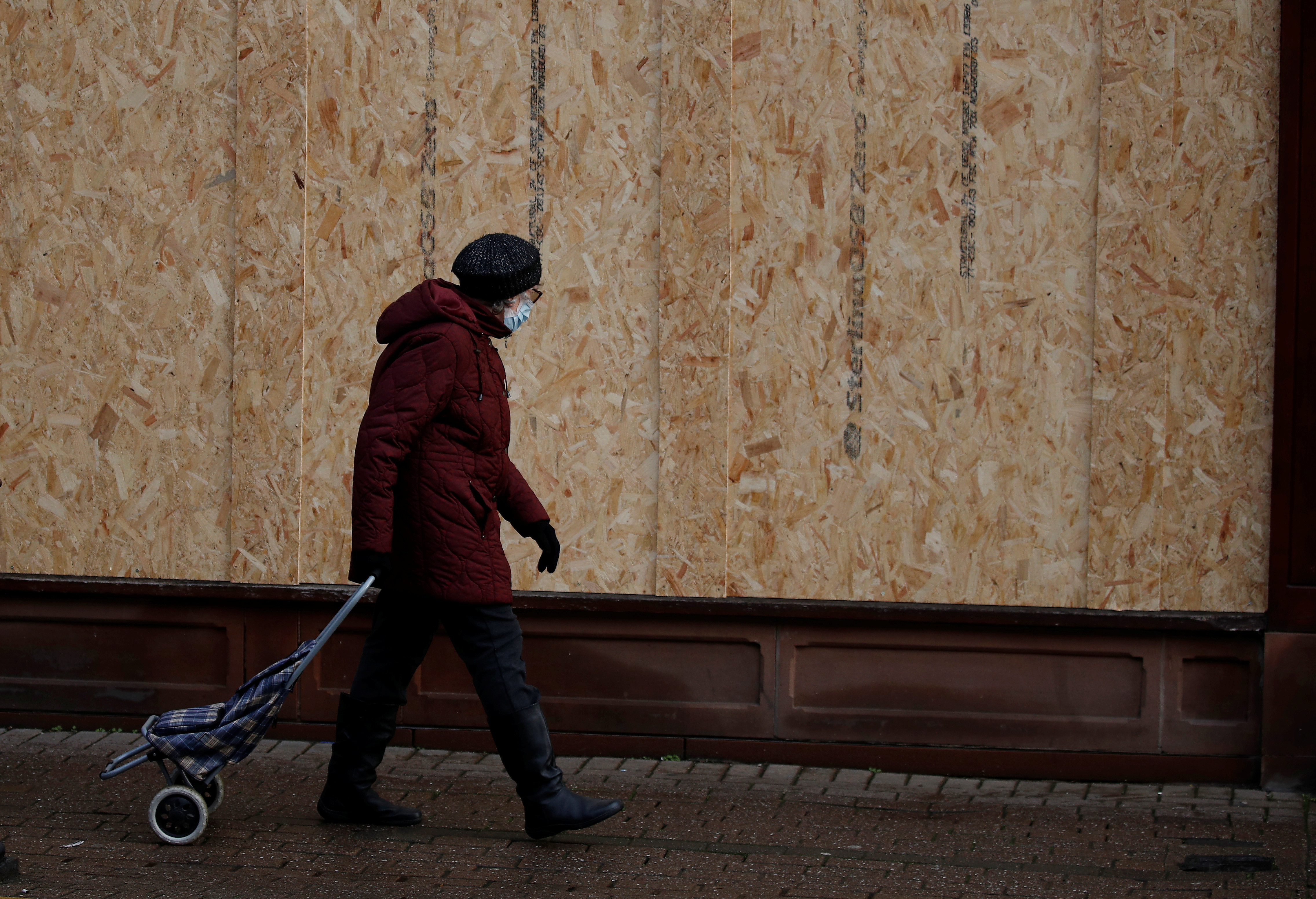 A woman walks past a boarded up retail unit amid the outbreak of the coronavirus disease (COVID-19) in Chester, Britain, December 8, 2020. Picture taken December 8, 2020. REUTERS/Phil Noble - RC2DKK9J373H
