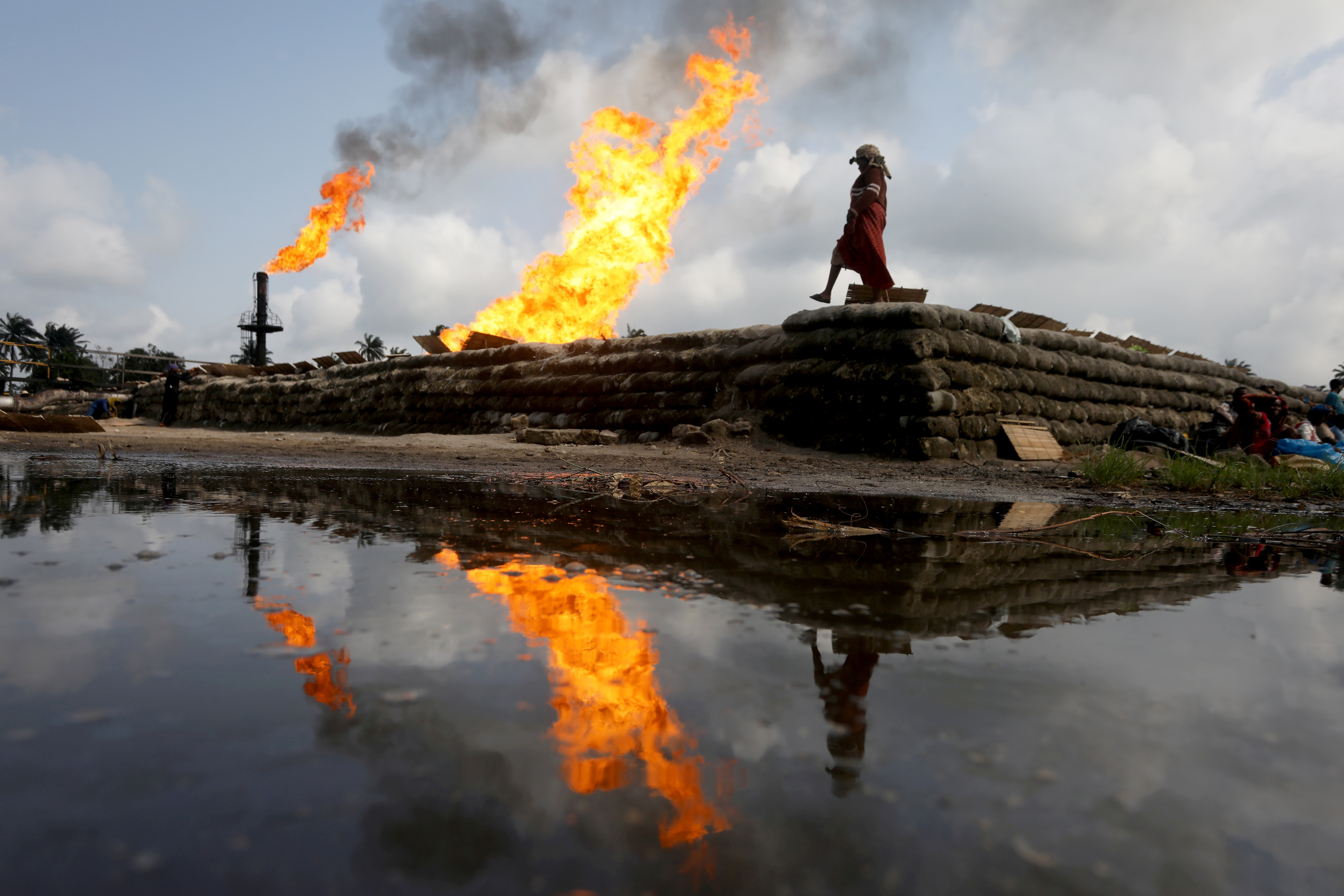 Two gas flaring furnaces and a woman walking on sand barriers are reflected in a pool of oil-smeared water at a flow station in Ughelli, Delta State, Nigeria September 17, 2020. Picture taken September 17, 2020.