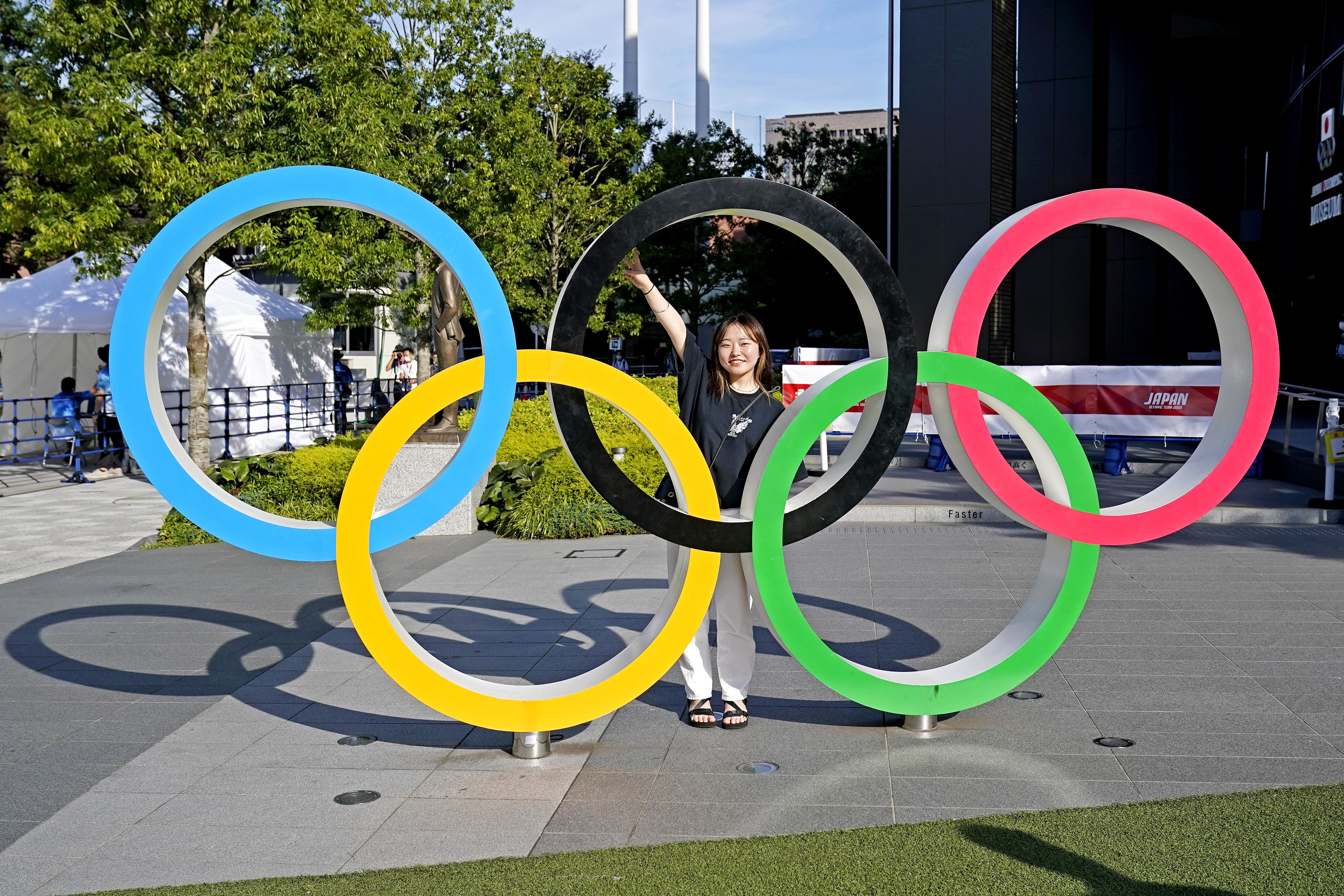 Tokyo, Japan; A women poses in front of the Olympic Rings outside the Olympic Stadium before the Tokyo 2020 Summer Olympic Games