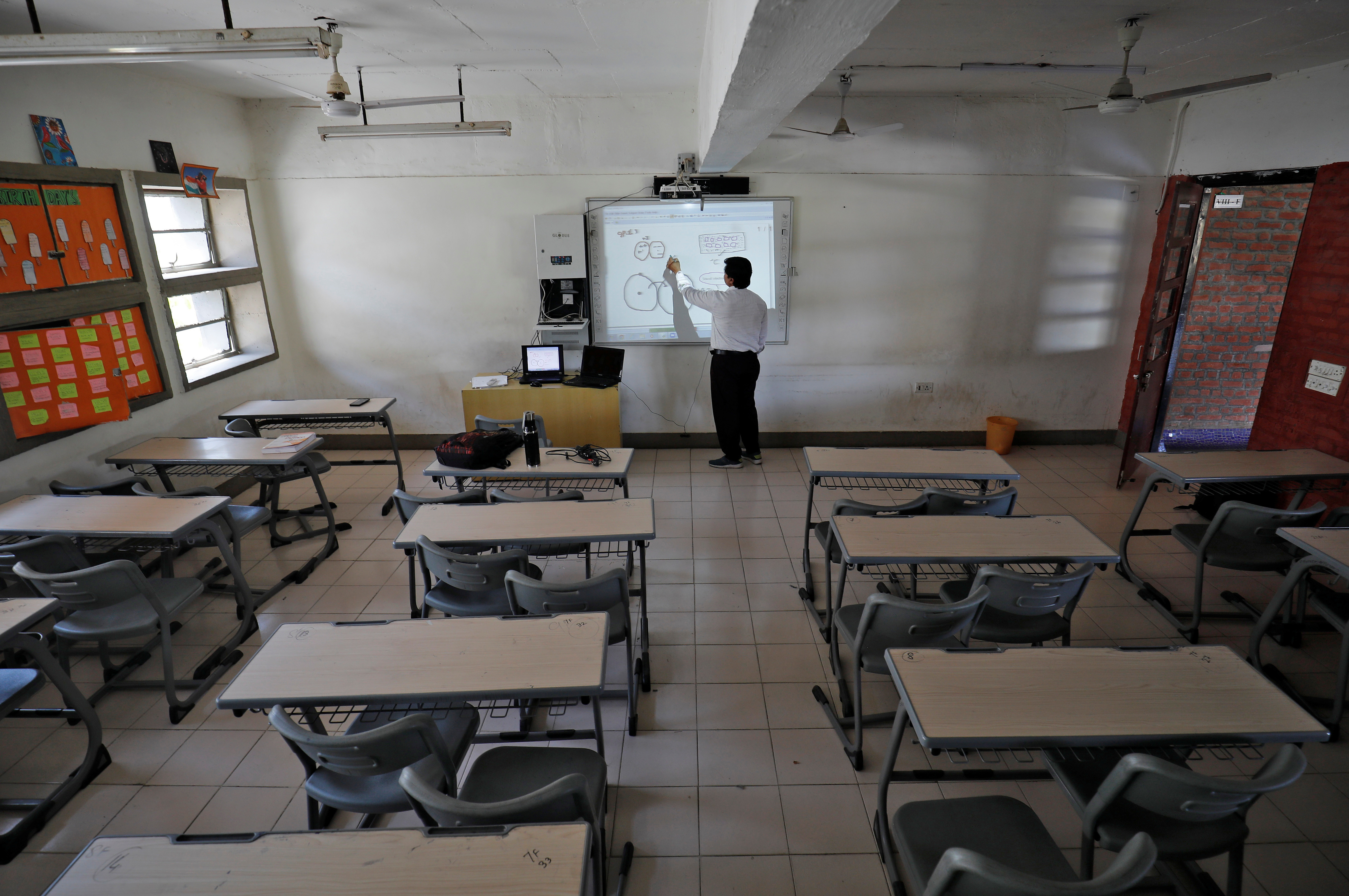 A teacher takes an online class for his students inside a private school after Gujarat government ordered the closure of schools and colleges across the state amid coronavirus fears, in Ahmedabad, India.