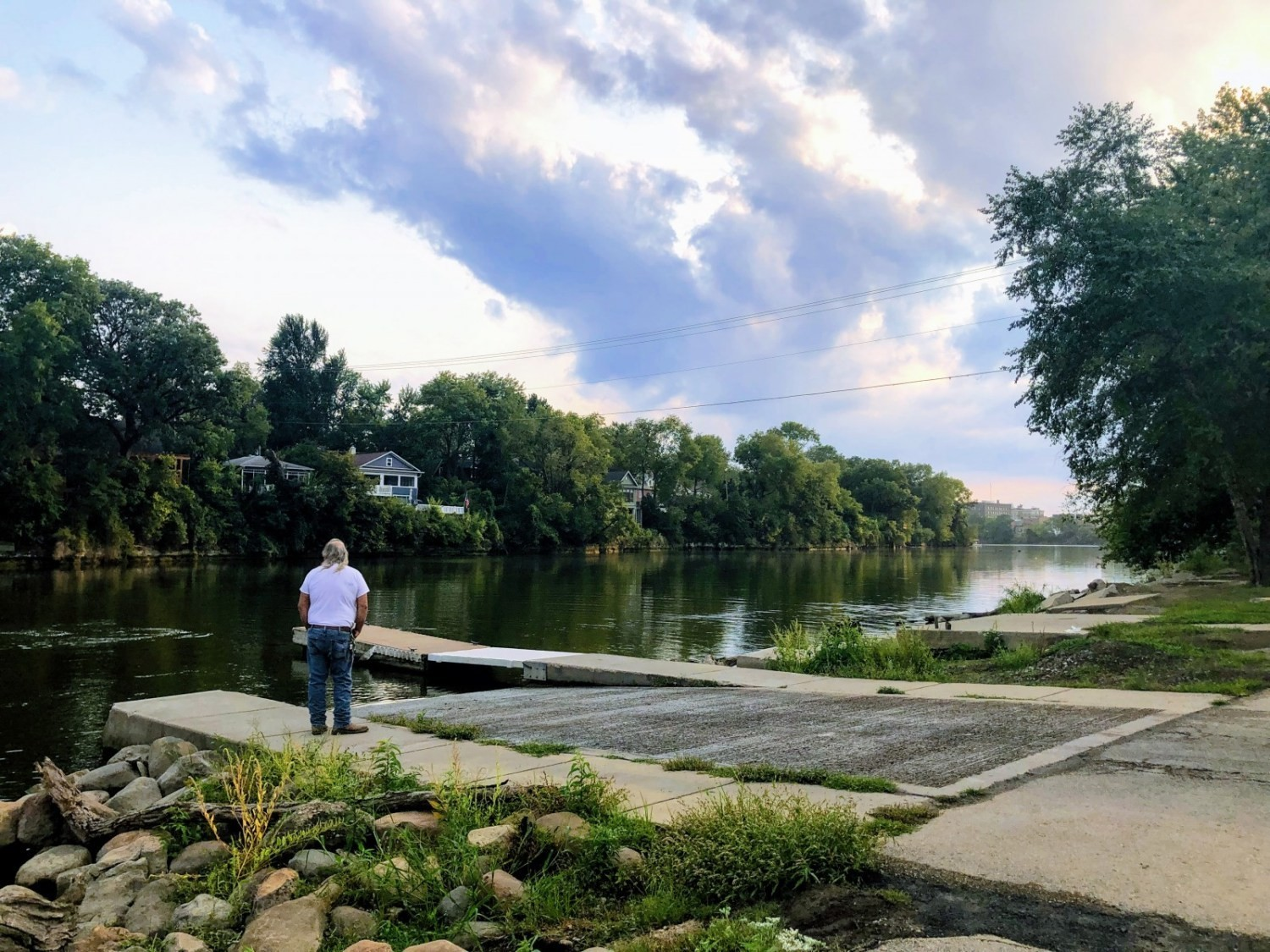 a man stands by the riverbank in Ottawa, Illinois, which has long been prone to flooding