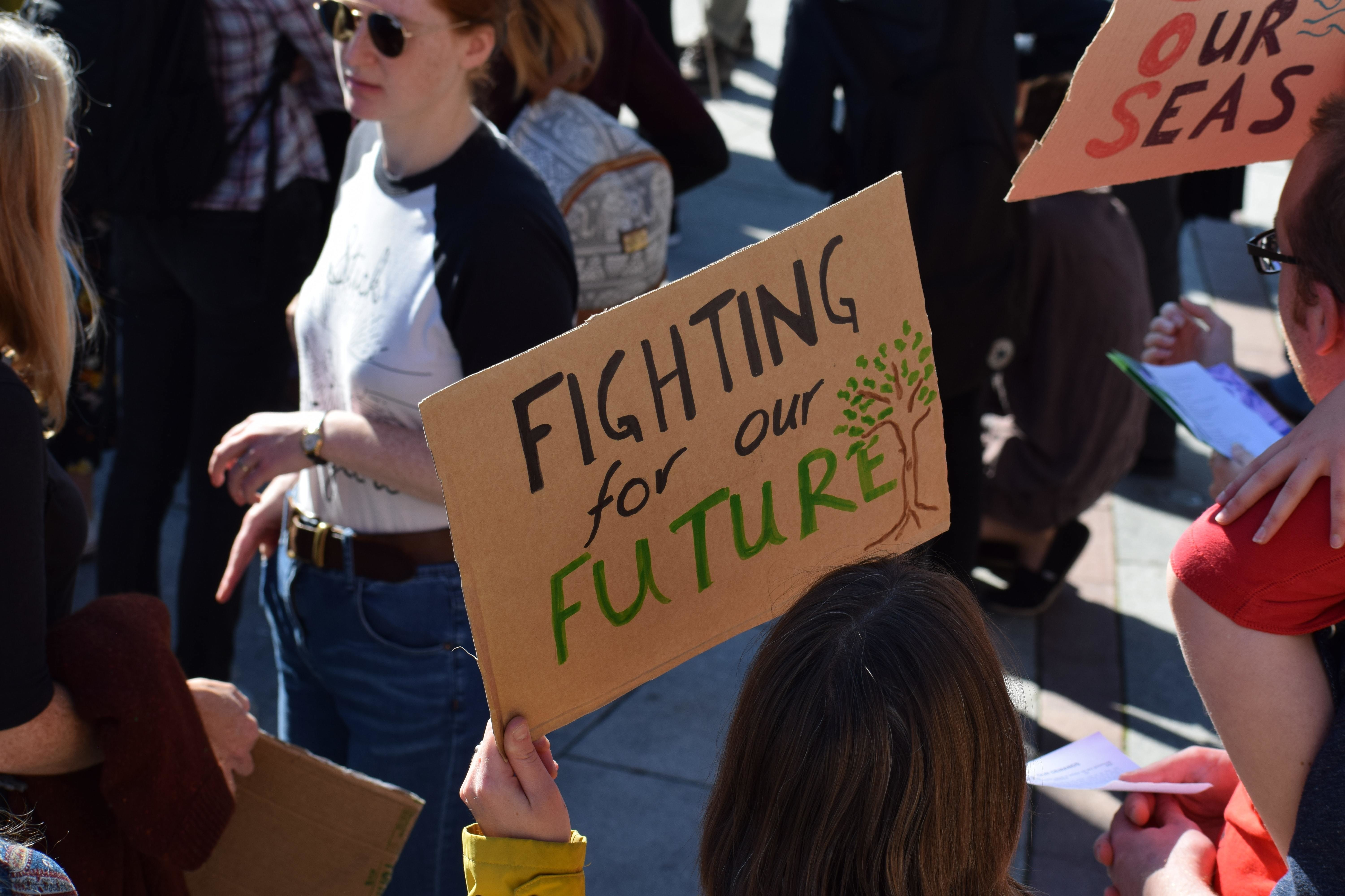 """placard held by young activists saying """"fighting for our future"""""""
