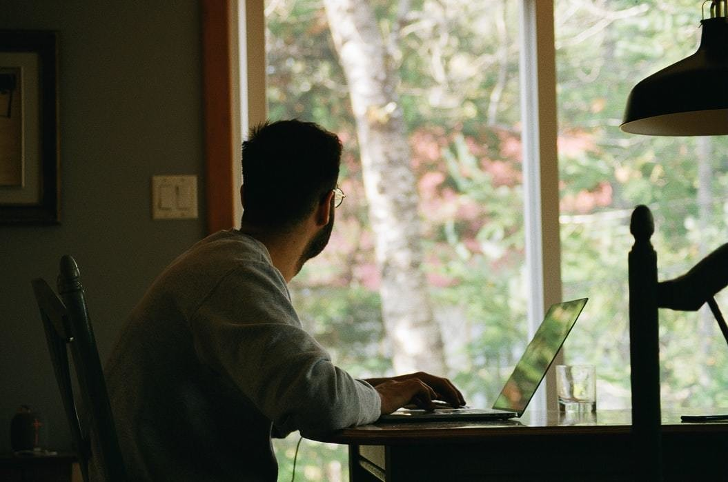 A man stares out of the window whilst working on his laptop at home.