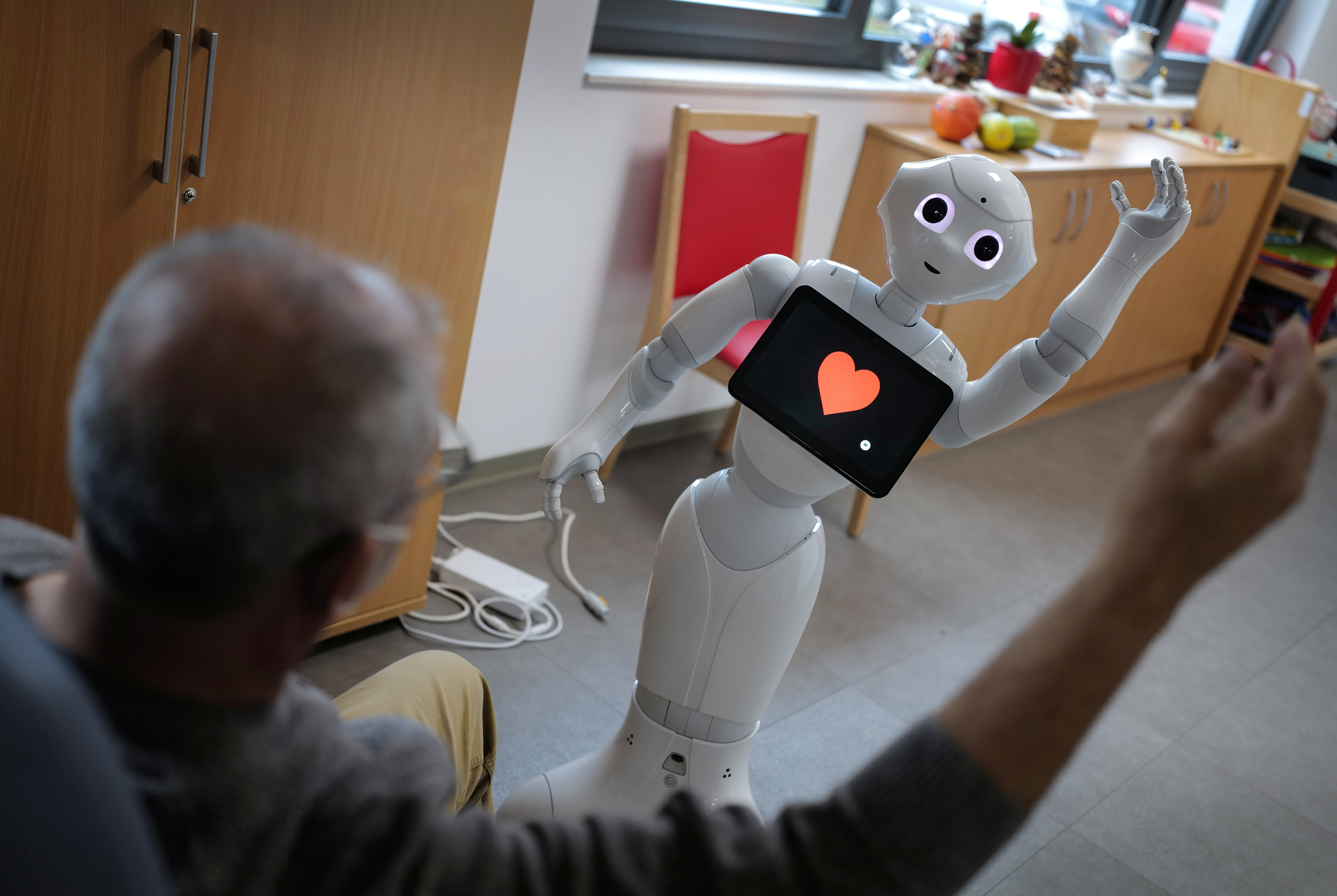 """A guest of the day care center of German welfare organisation Caritas follows the instructions of humanoid robot """"Pepper"""" for his rehabilitation work out as the spread of the coronavirus disease (COVID-19) continues in Erlenbach, 50 km south of Frankfurt, Germany, November 25, 2020. Picture taken November 25, 2020. REUTERS/Kai Pfaffenbach - RC2VAK9MCXBV"""