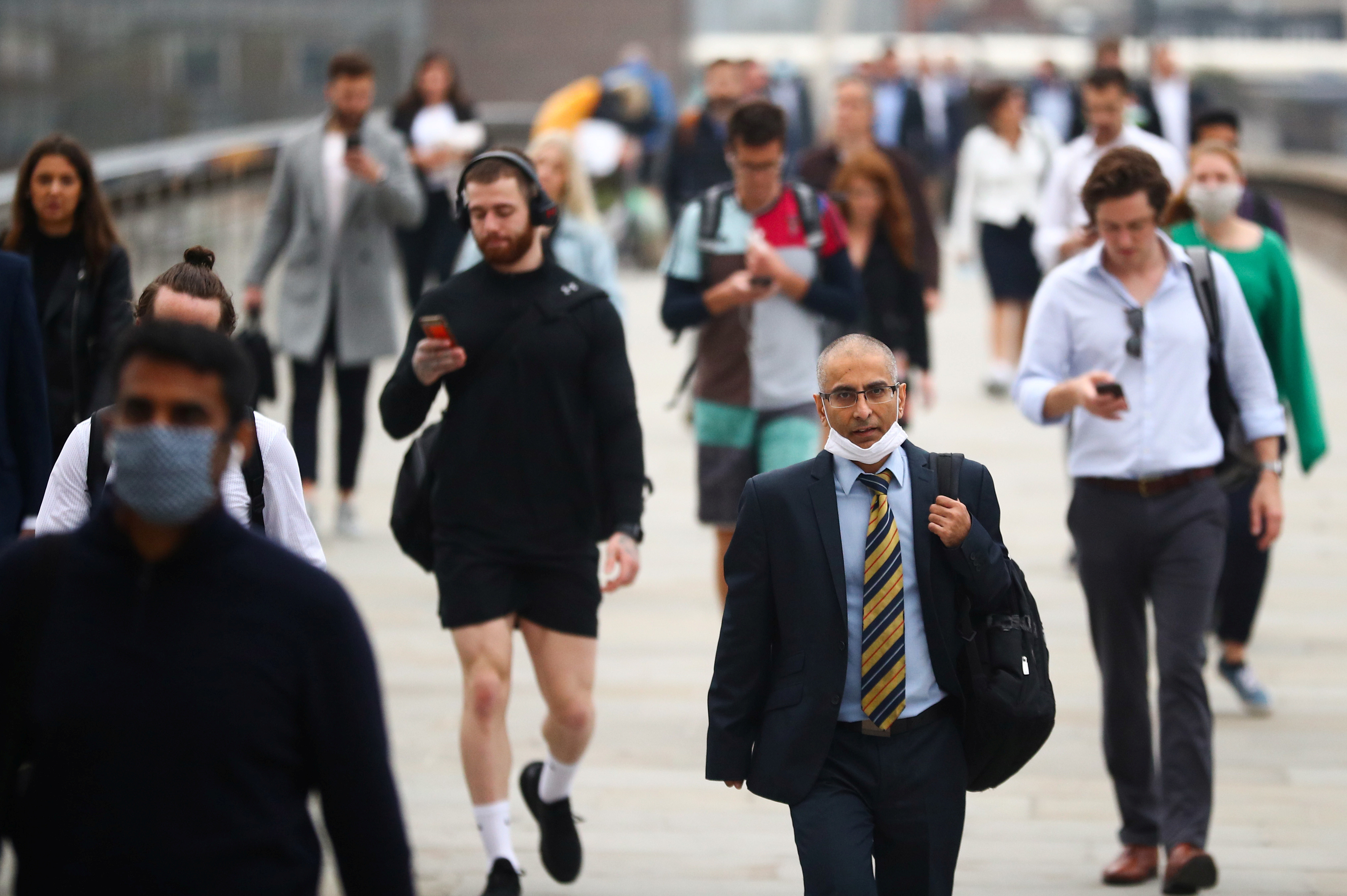 Commuters walk across the London Bridge during the morning rush hour, amid an outbreak of the coronavirus disease (COVID-19), in London, Britain September 21, 2020. REUTERS/Hannah McKay - RC2W2J9FPD3A