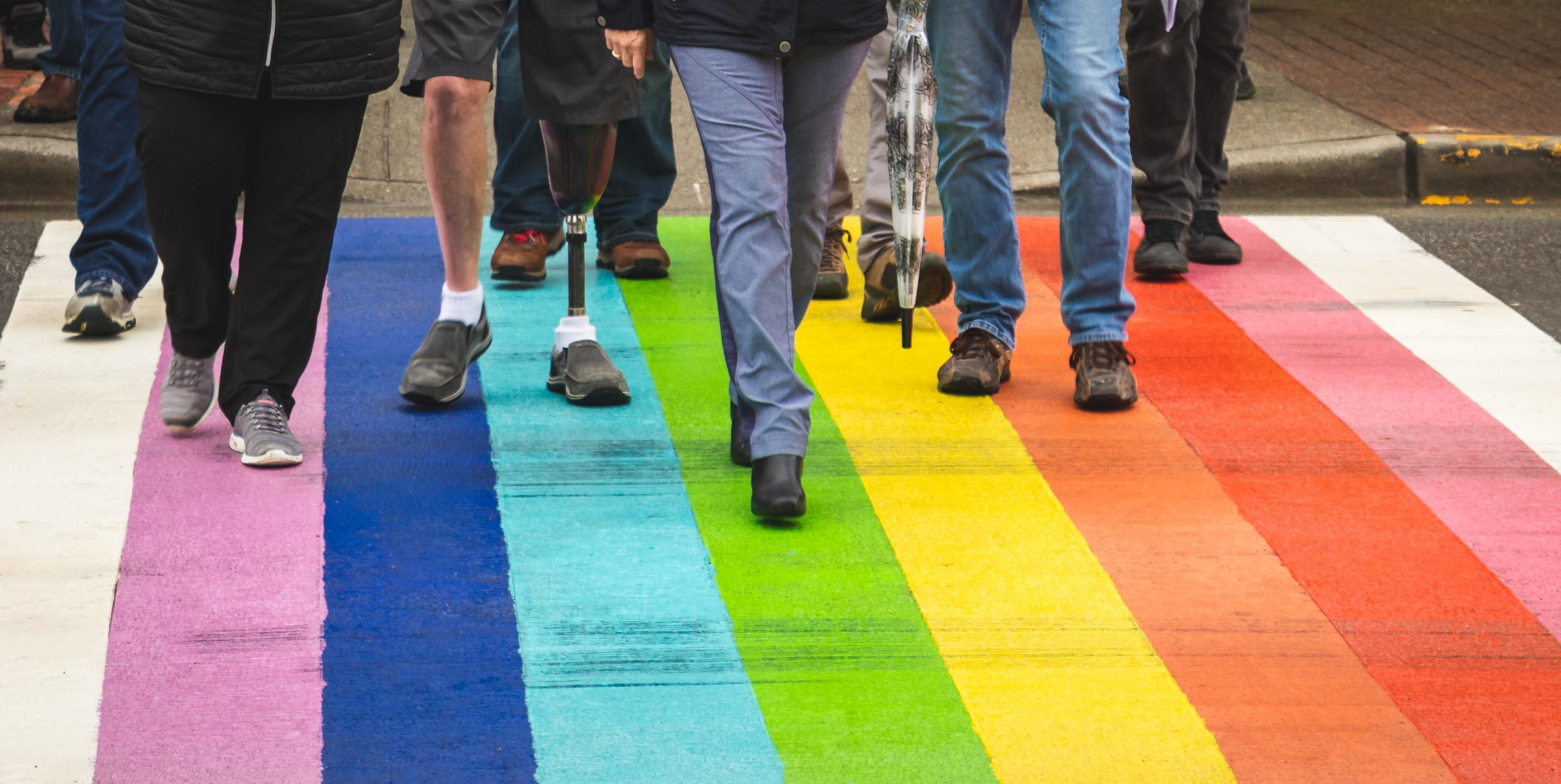 a diverse group of people walk across a pedestrian crossing with rainbow colours to signify the LGBTQ+ movement