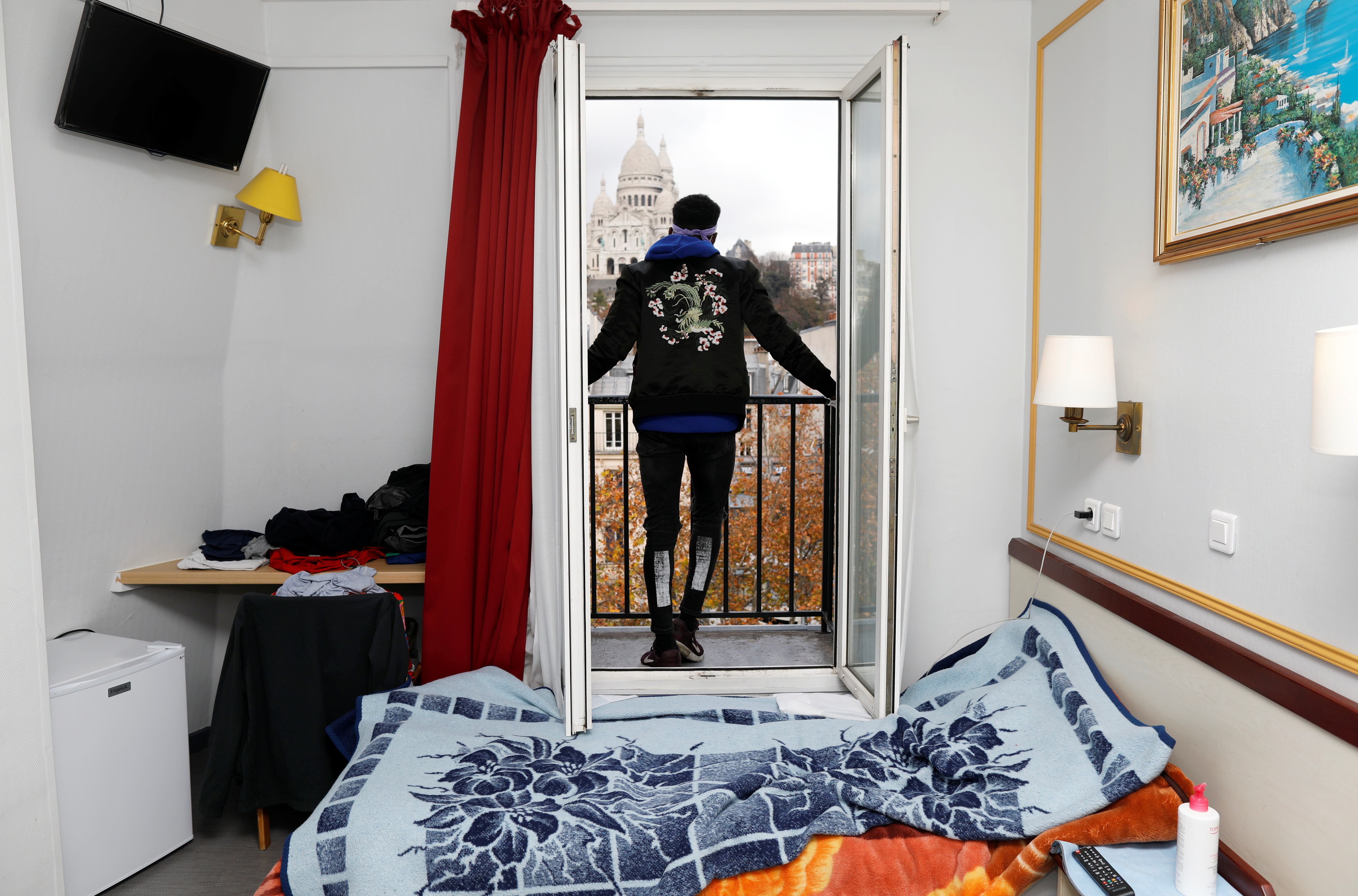 Asylum-seeker Ibrahim looks at the Sacre Coeur Cathedral from his room at the Hotel Avenir Montmartre in Paris, France, December 2, 2020. The hotel, deserted by tourists due to COVID-19 travel bans opens its 42 rooms to the city's homeless for 12 months with the help of French charity association Emmaus Solidarite. Picture taken December 2, 2020.  REUTERS/Charles Platiau - RC2MFK9CW7TY