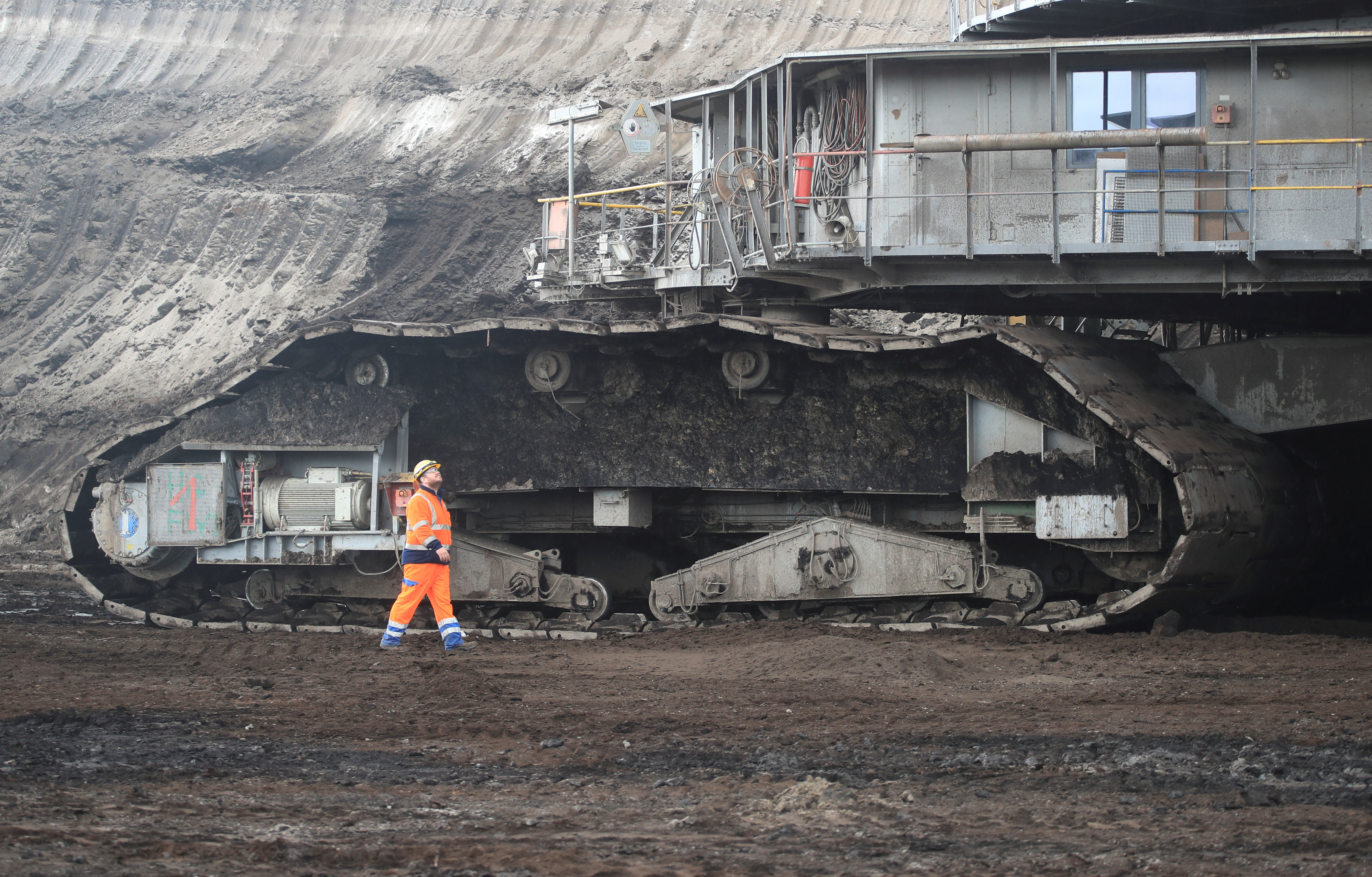 An operator of RWE's huge bucket wheel excavator walks in front of the chain wheels of the paddle-wheel digger in the open-cast brown coal mine of Inden near Weisweiler after an Internet auction ended to sell the 3,500 tons heavy excavator, in Inden, Germany September 30, 2020.
