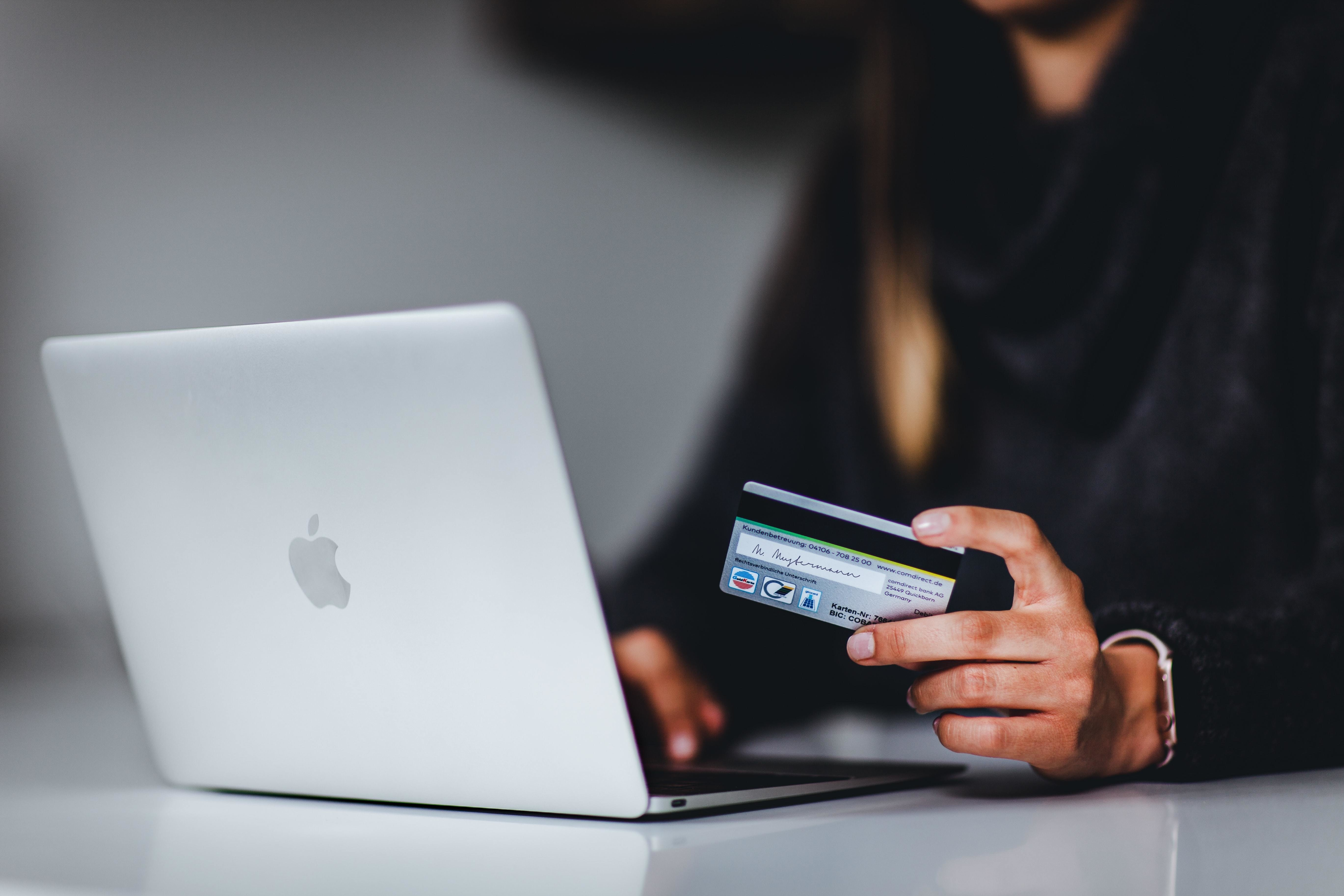 a picture of a woman using her credit card to buy something online