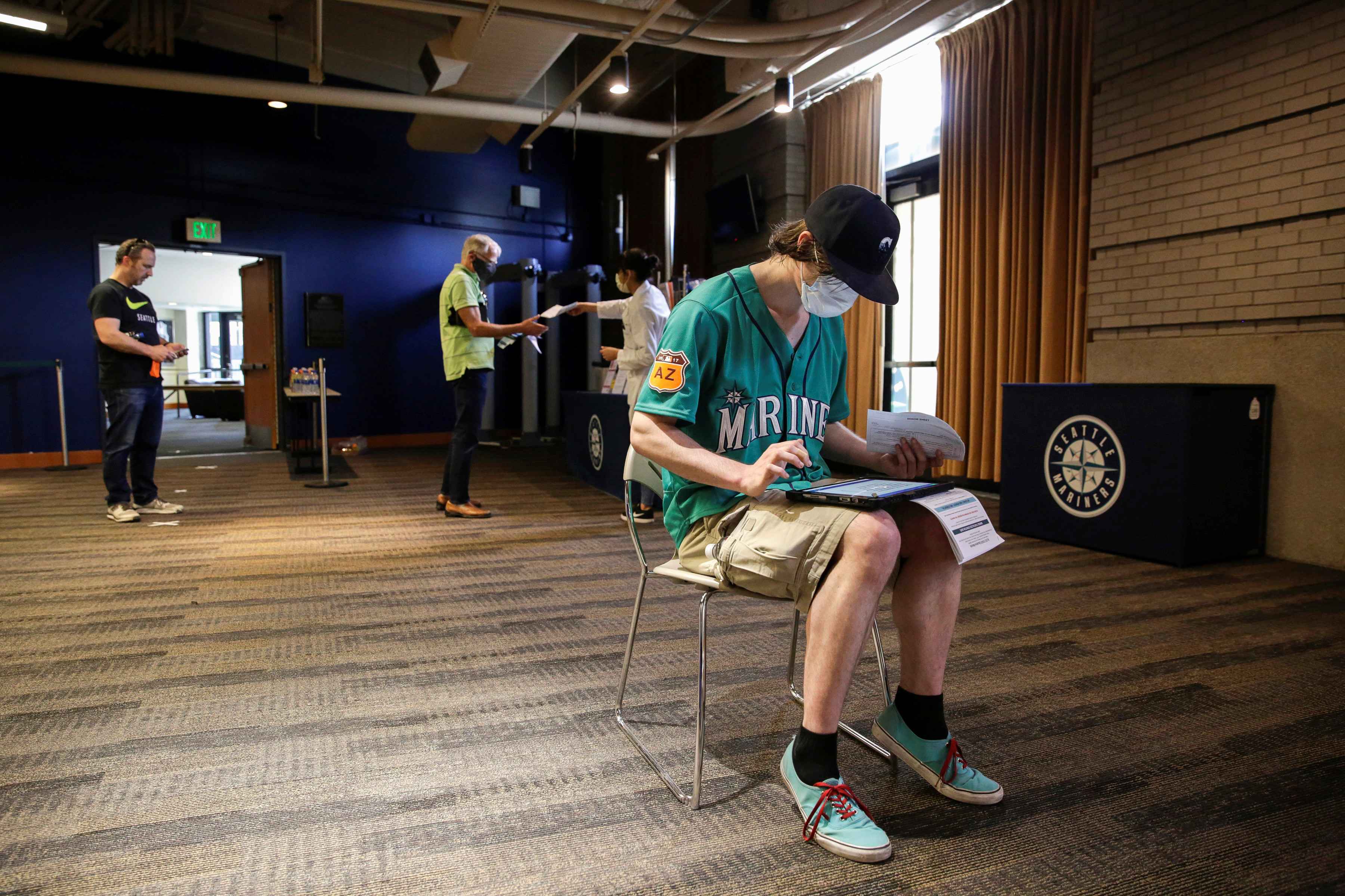 Craig McCall of Tacoma, Washington, who was furloughed from his job at the Emerald Queen Casino, fills out paperwork to donate blood during a Pop-Up Blood Drive experience at T-Mobile Park, the stadium of Major League Baseball's Seattle Mariners, as efforts continue to help slow the spread of the coronavirus disease (COVID-19) in Seattle, Washington, U.S. April 13, 2020.