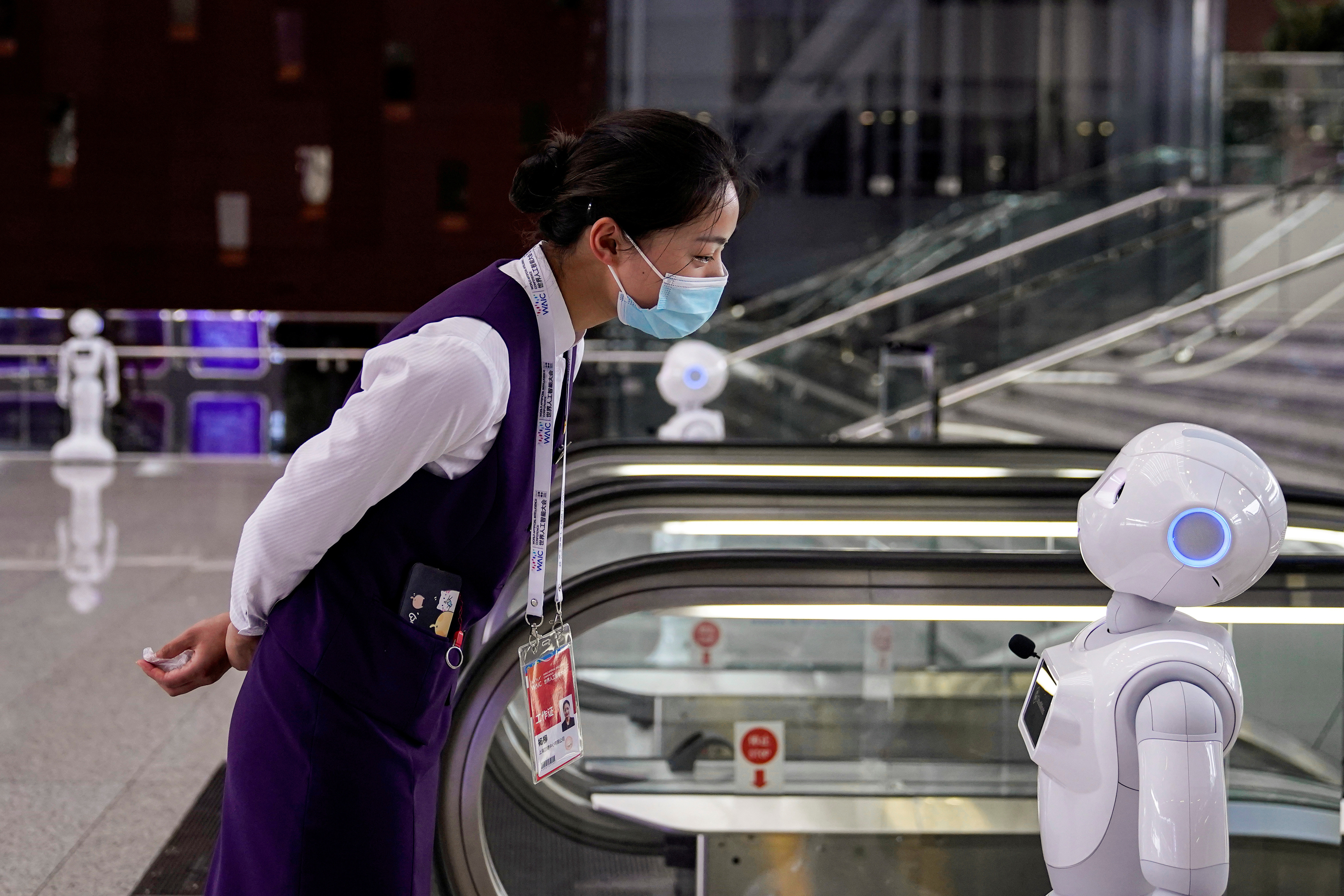 A staff member, wearing a face mask following the coronavirus disease (COVID-19) outbreak, looks at a robot at the venue for the World Artificial Intelligence Conference (WAIC) in Shanghai, China