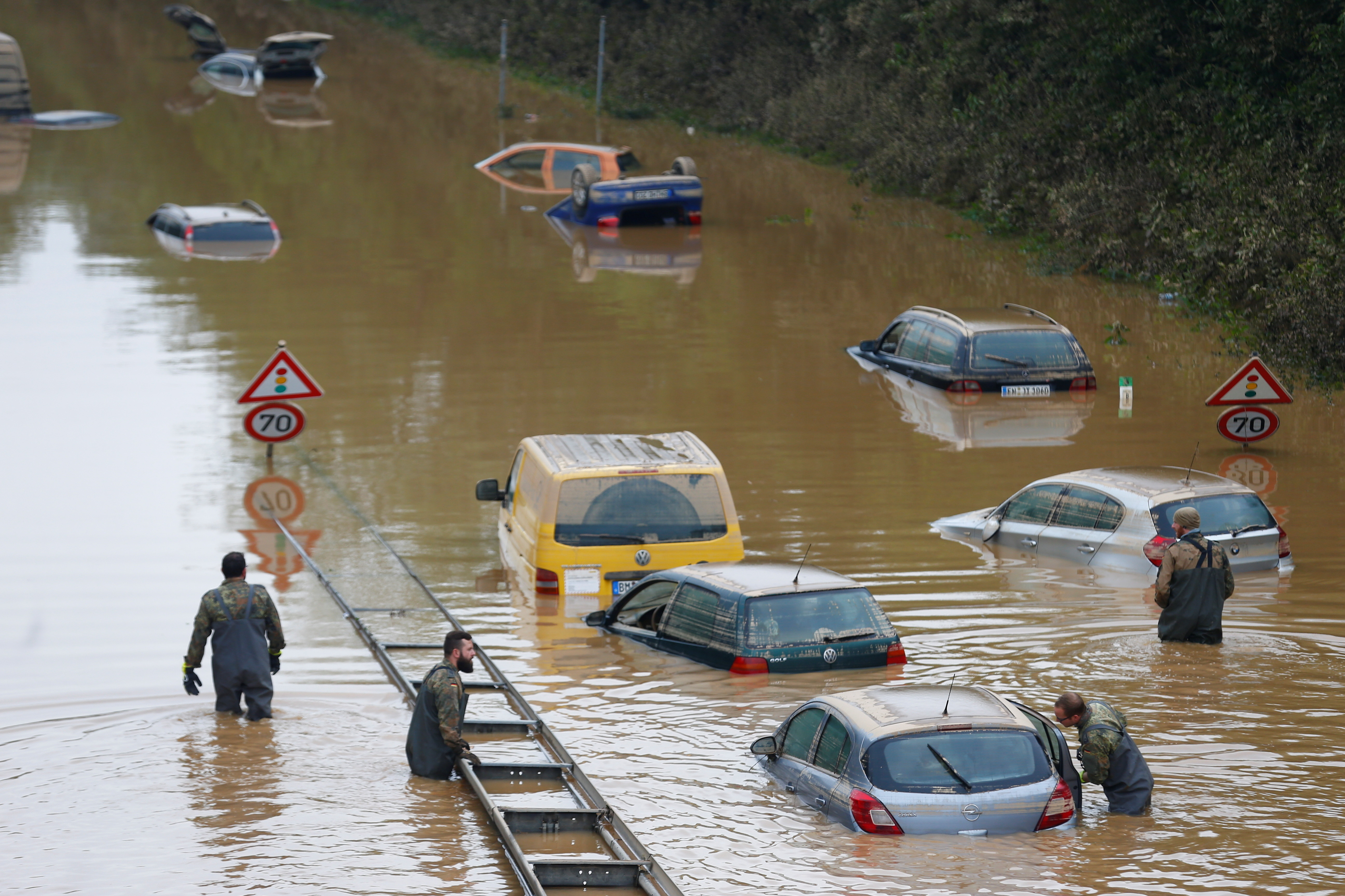 Members of the Bundeswehr forces, surrounded by partially submerged cars, wade through the flood water following heavy rainfalls in Erftstadt-Blessem, Germany