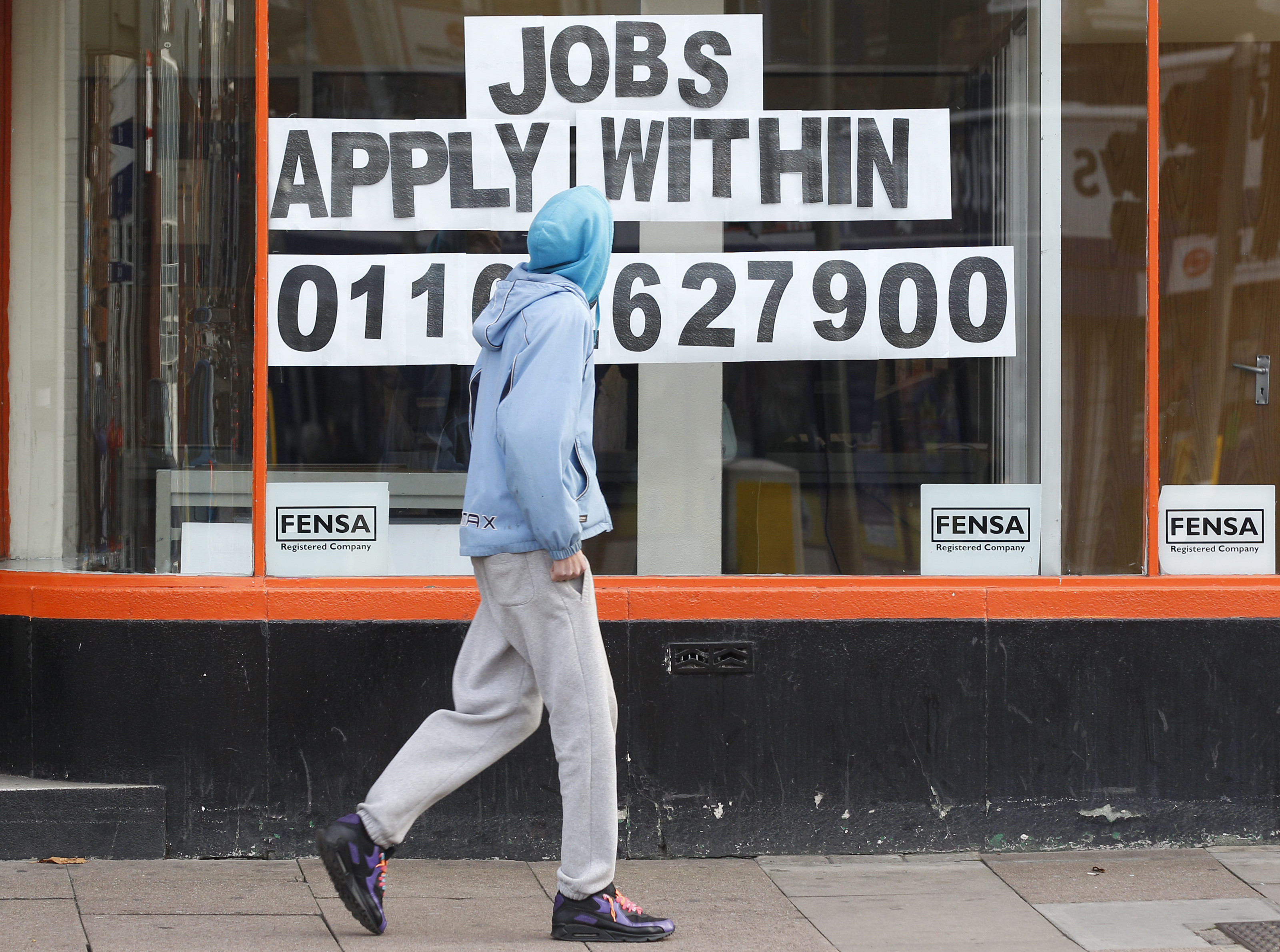 A man walks past a shop advertising job vacancies in Leicester, central England November 16, 2011. Unemployment in Britain hit its highest in 15 years and the number of young people out of work soared to a record of more than 1 million, adding to pressure on the government to do more to support a faltering economy.     REUTERS/Darren Staples (BRITAIN - Tags: BUSINESS POLITICS EMPLOYMENT) - LM1E7BG10KS01